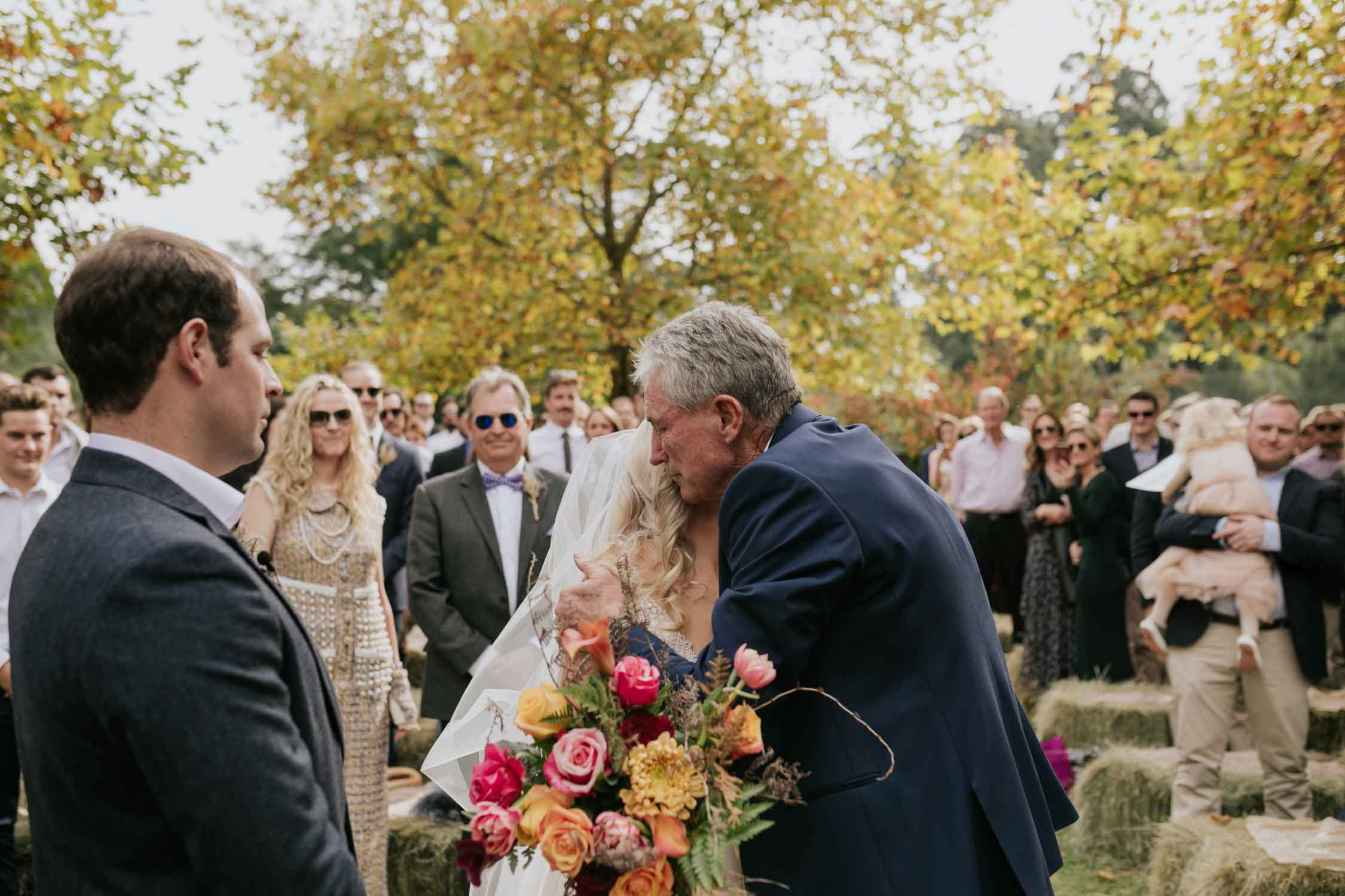 Bride and father embracing at the top of the aisle before he hands her over to her groom. Bride wearing a low cut dress with beautiful and detailed beadwork with a skirt that is see through and cute shorts underneath almost like a jump suit underneath a wedding dress. She is holding a wedding bouquet of burnt orange pink and red flowers and roses with dried ferns and grass in it.