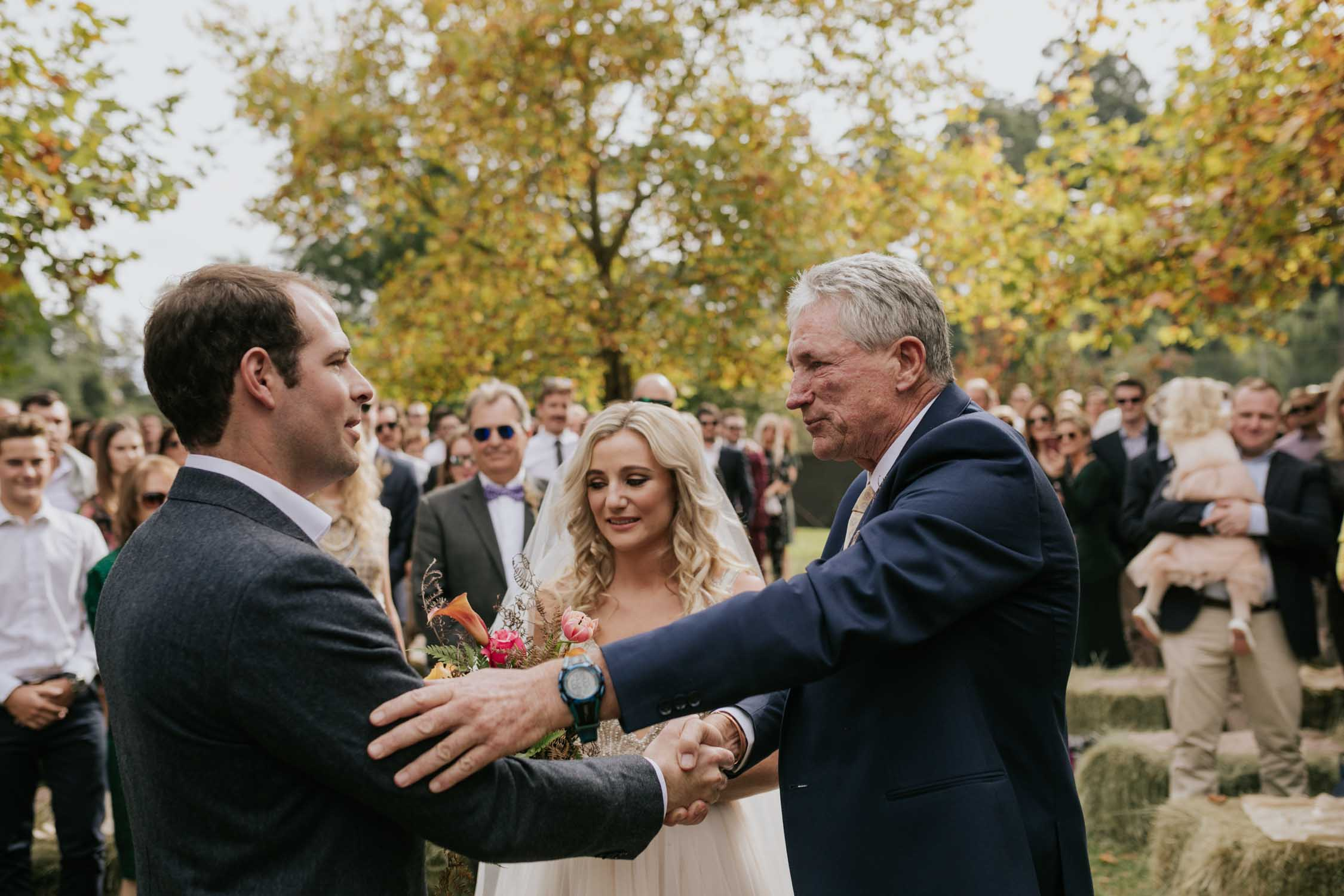 Bride's father embracing and holding onto groom's arm as he hands over his daughter to the groom at the top of the aisle. Very emotional wedding moment.