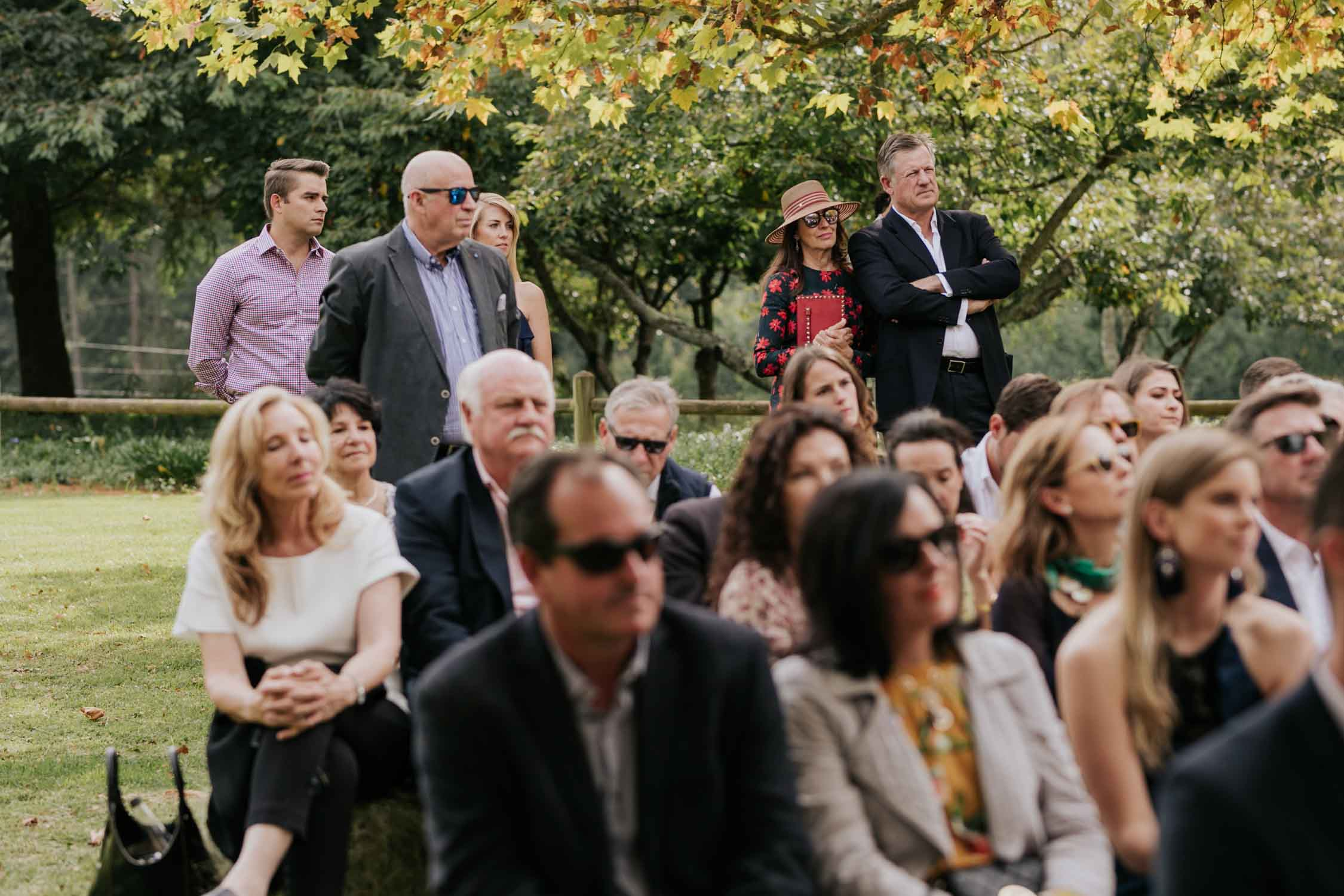 Guests watching bride and groom get married under Autumn trees during wedding ceremony on a farm