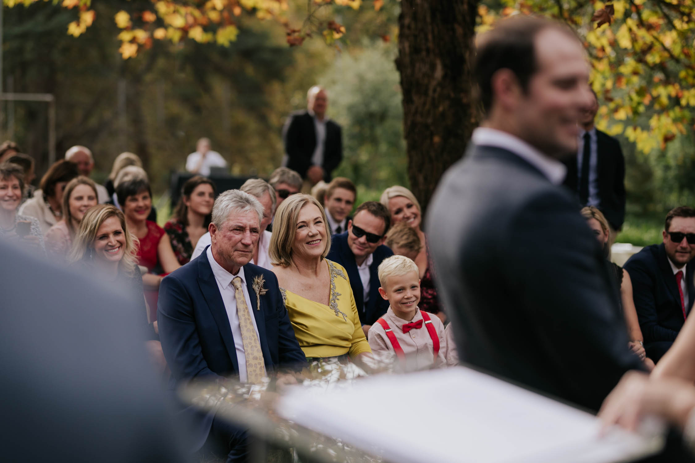 Bride's parents during ceremony watching their daughter get married. Emotional Wedding Photography. Candid moment.