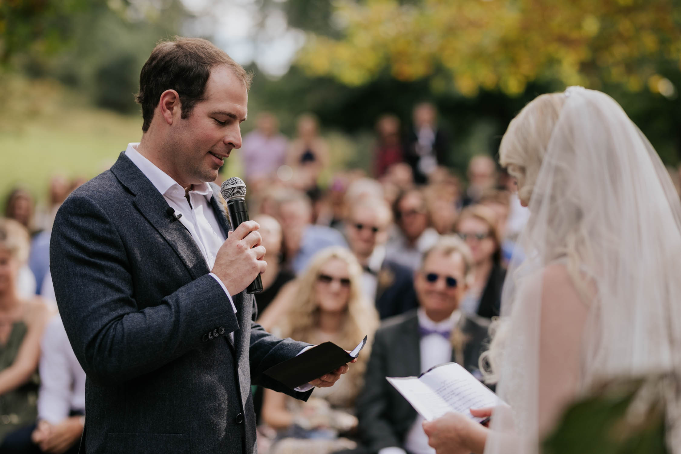 Groom saying his vows to the bride. Bride wearing a low cut dress with beautiful and detailed beadwork with a skirt that is see through and cute shorts underneath almost like a jump suit underneath a wedding dress. She is holding a wedding bouquet of burnt orange pink and red flowers and roses with dried ferns and grass in it.