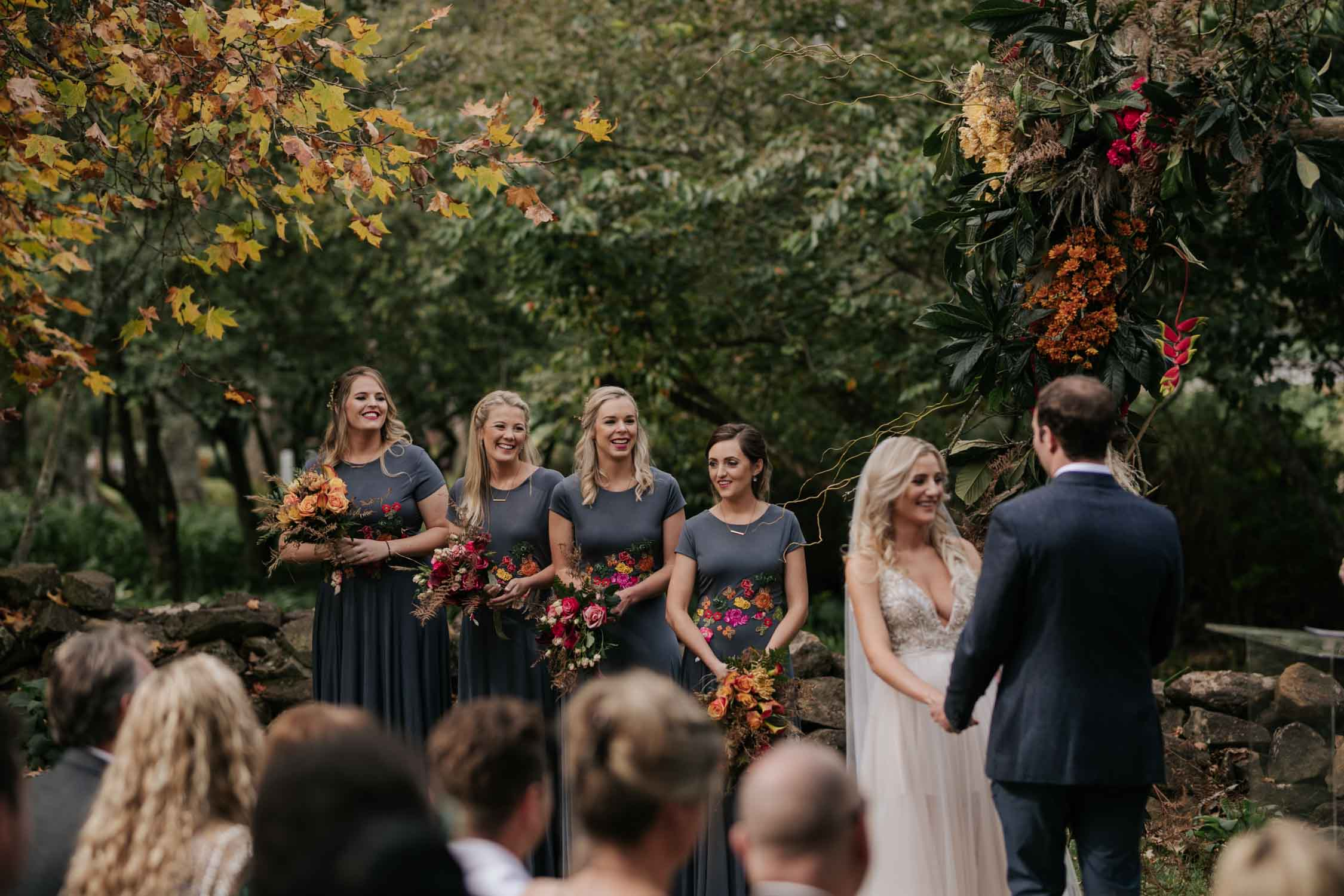 Bridesmaids standing in front at wedding ceremony watching the bride and groom say vows. Bridesmaids are wearing tight grey wedding dresses with high necklines. Bride wearing a low cut dress with beautiful and detailed beadwork with a skirt that is see through and cute shorts underneath almost like a jump suit underneath a wedding dress. She is holding a wedding bouquet of burnt orange pink and red flowers and roses with dried ferns and grass in it.