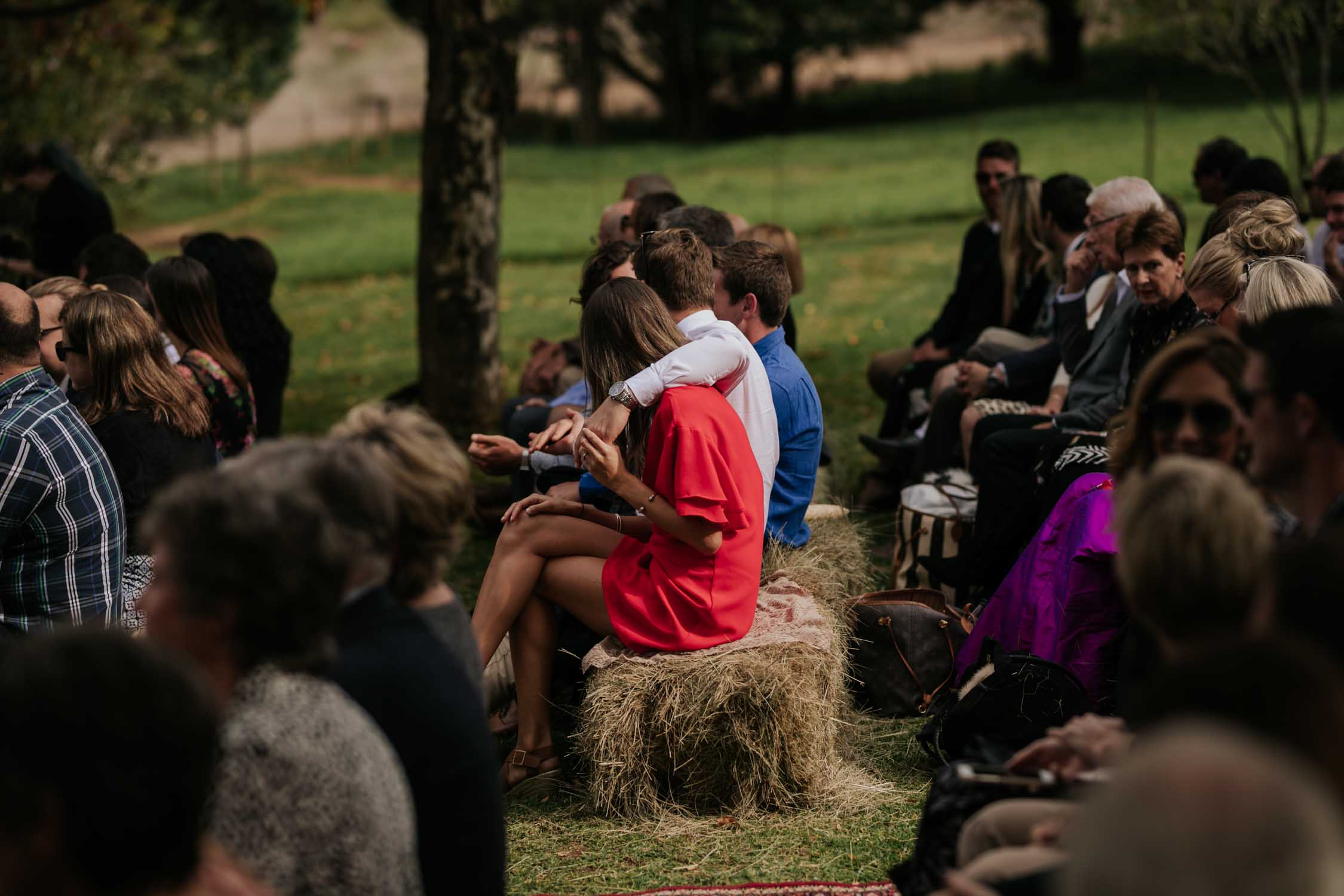 Guests sitting on hay bales on farm during the wedding ceremony on dairy farm.