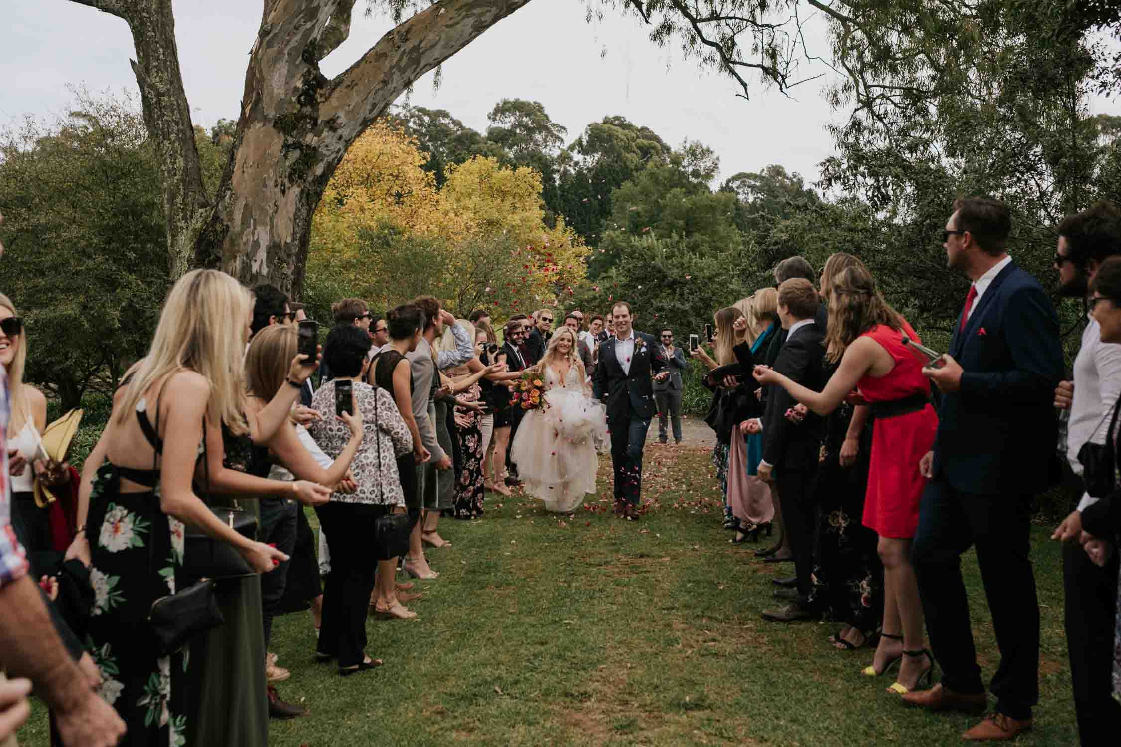 Bride and groom walking down an aisle of friends and family laughing during confetti toss. Emotional moment and photo of bride looking at groom saying his vows during ceremony. Bride wearing a low cut dress with beautiful and detailed beadwork with a skirt that is see through and cute shorts underneath almost like a jump suit underneath a wedding dress. She is holding a wedding bouquet of burnt orange pink and red flowers and roses with dried ferns and grass in it.