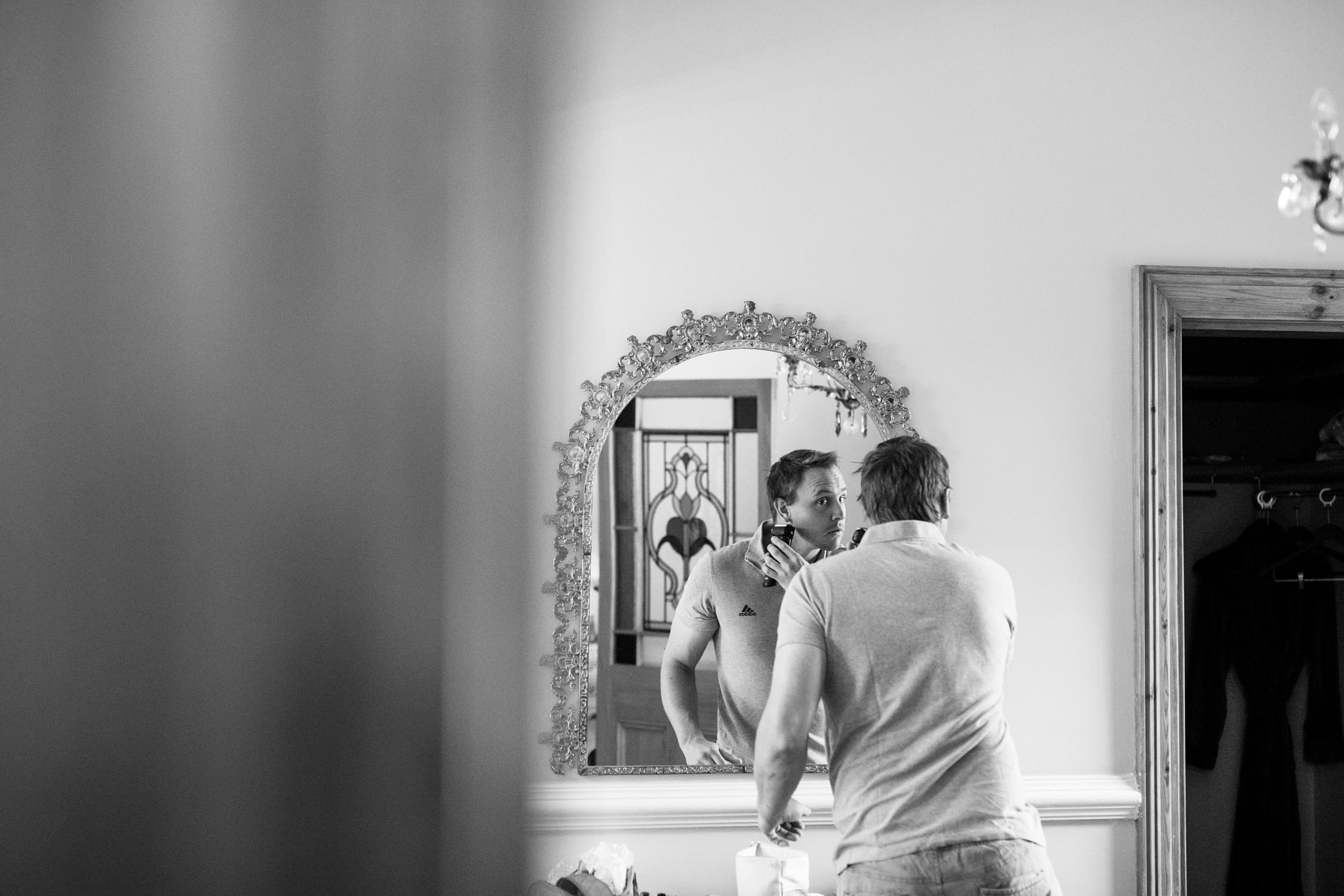 Natural documentary photograph of groomsman shaving with his reflection in a mirror