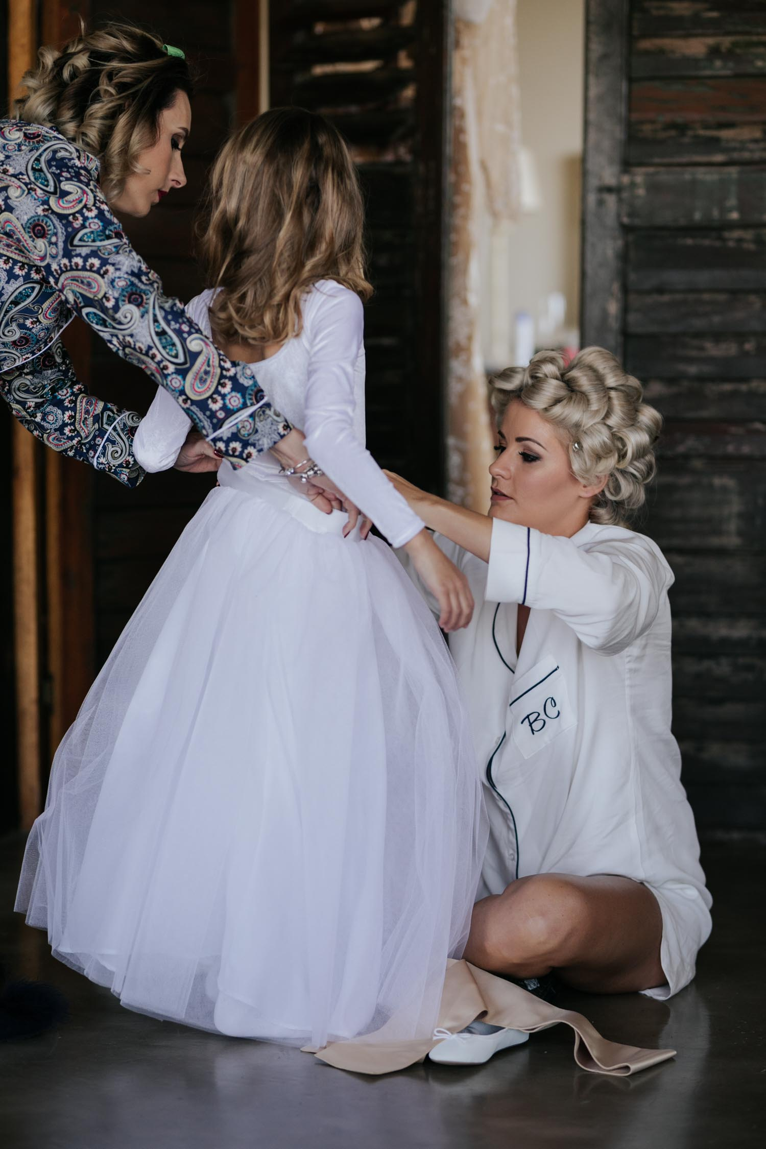 Bride helping the flower girl get ready on her wedding day