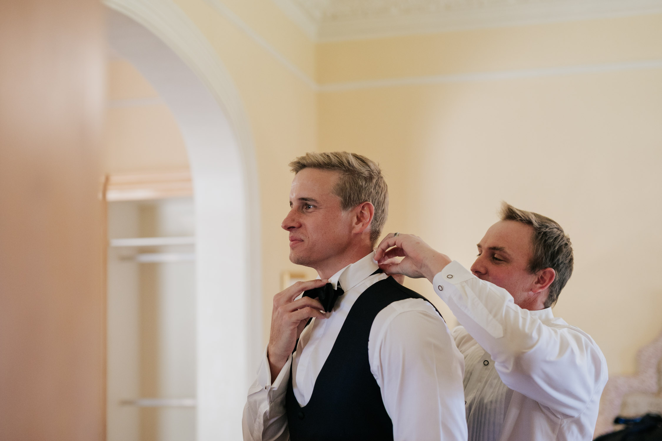 Groomsman helping the groom get ready. Groom's outfit is black tie and a black waistcoat with a white shirt.