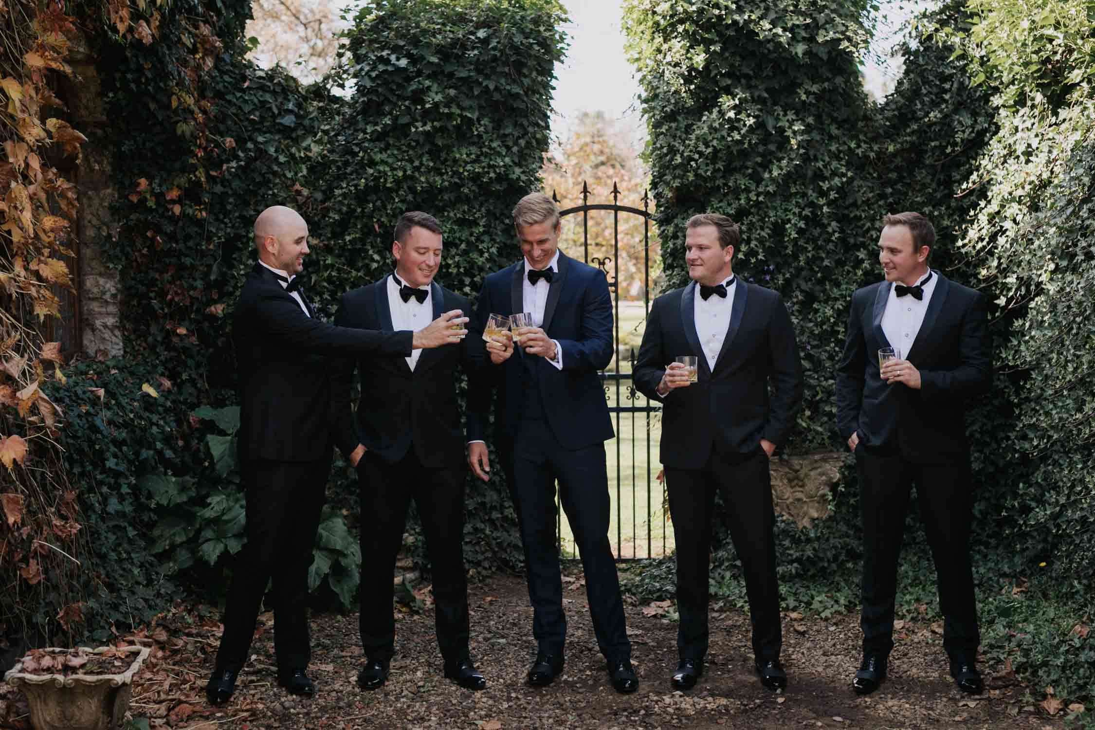 Groom standing with his groomsmen before his wedding ceremony laughing and having a drink of whiskey