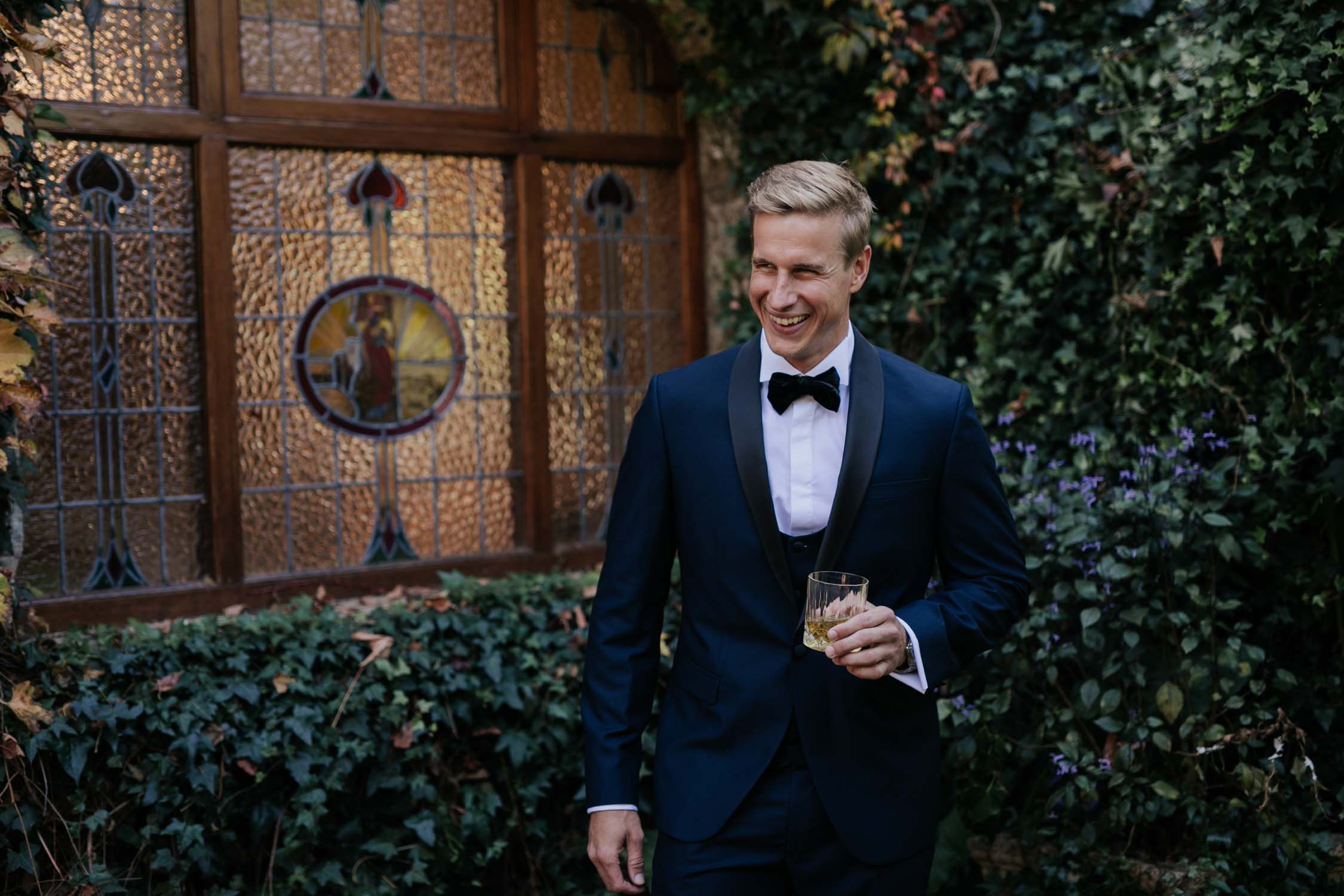 Groom dressed in black tie drinking whisky and laughing before his wedding at Hartford House Wedding Venue in the Natal Midlands