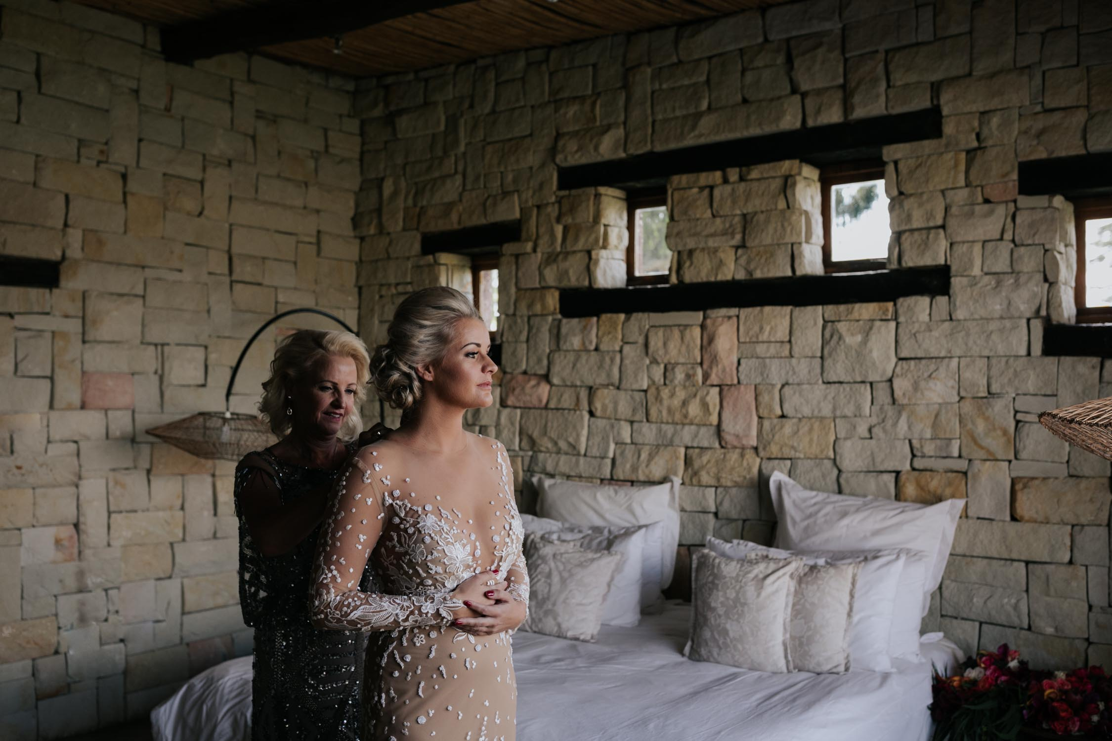 Mother of the bride helping the bride get into her nude dress with white floral embodied detail at Hartford House a wedding venue in the Natal Midlands