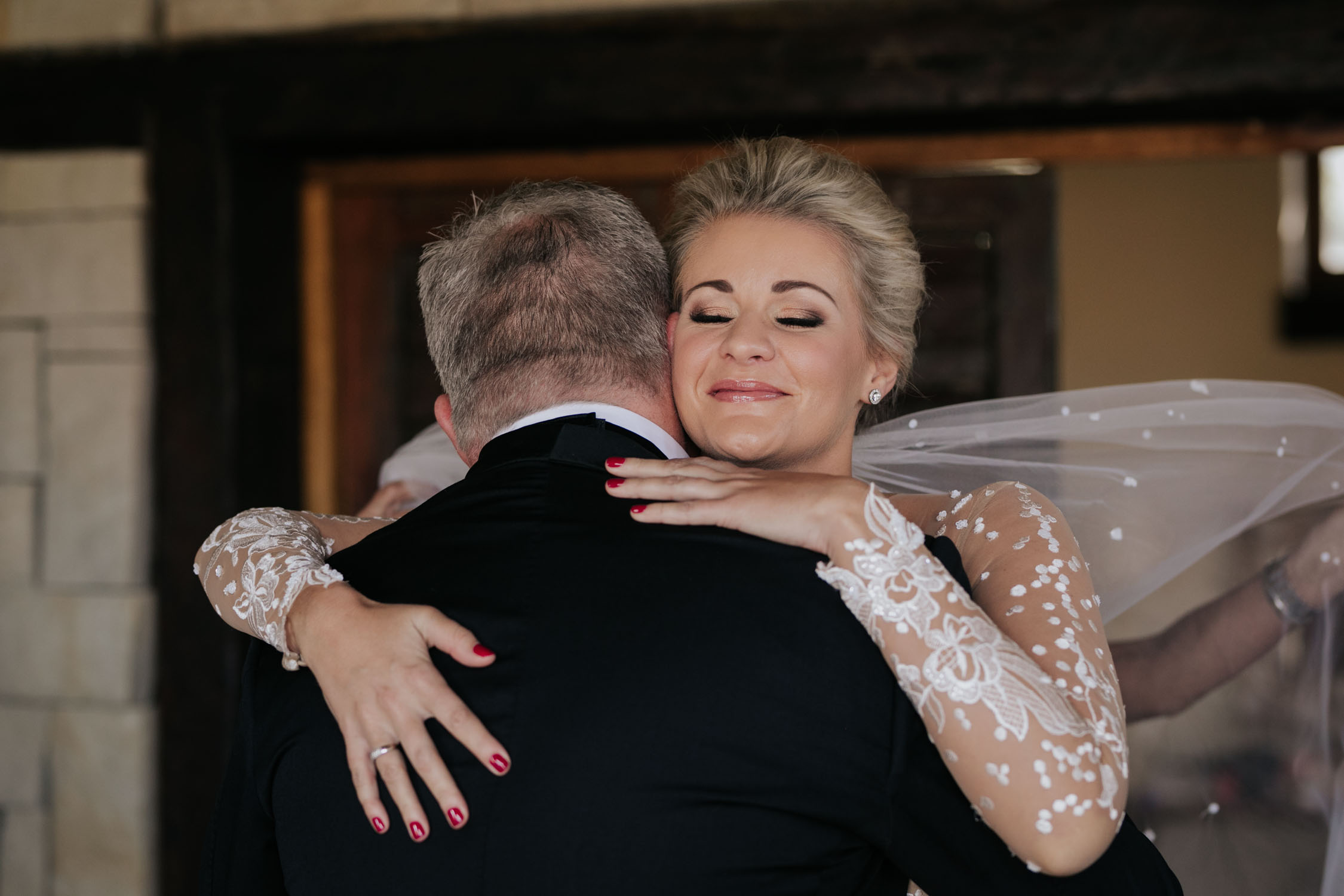 Emotional moment of bride and bride's father hugging when he sees her for the first time