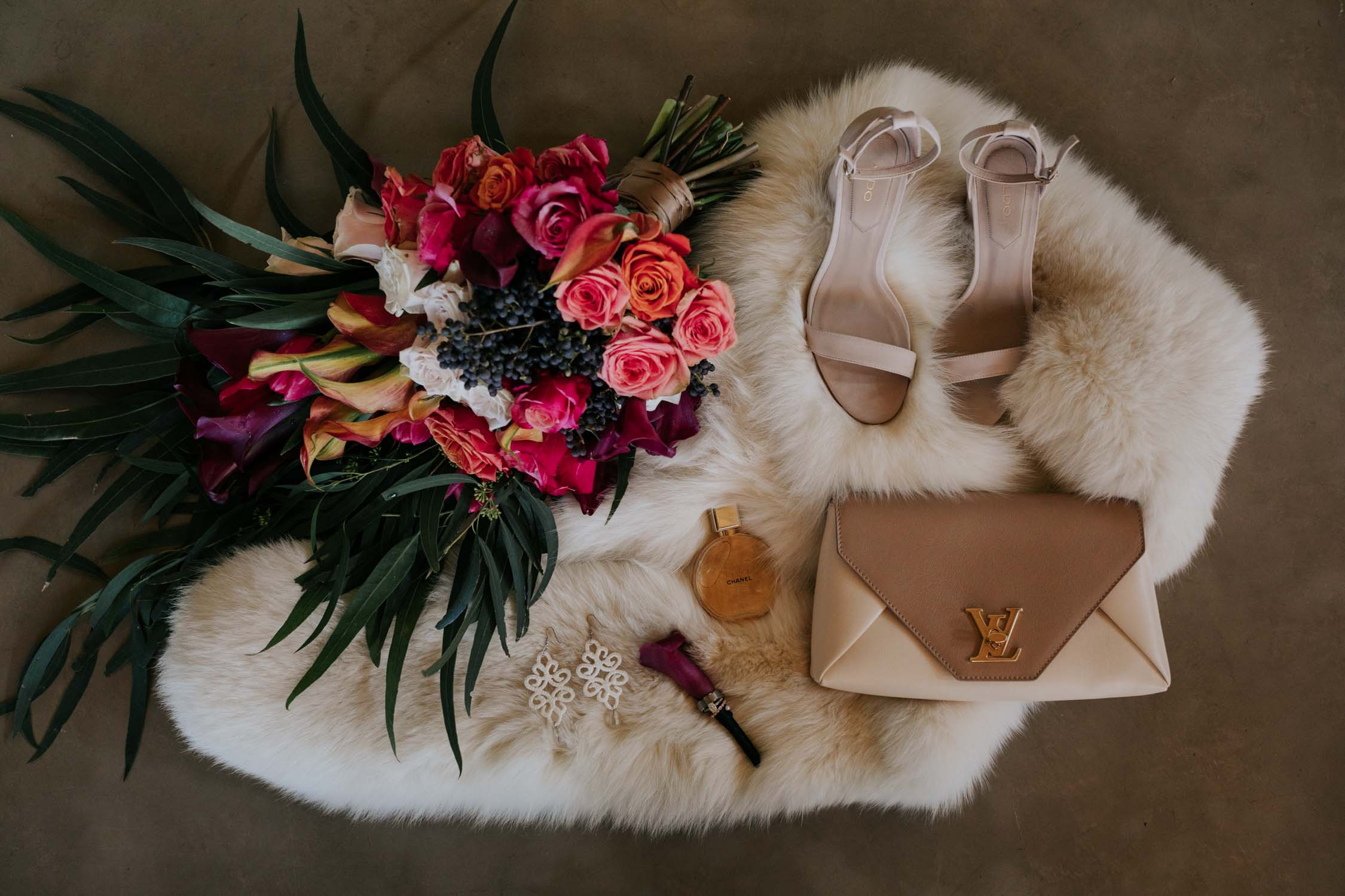 A flat lay of a bride's wedding accessories - her bright jewel coloured bouquet with burnt orange and pink roses and purple tulips, a soft white fur, nude open shoes, a Louis Vuitton clutch bag and a her perfume