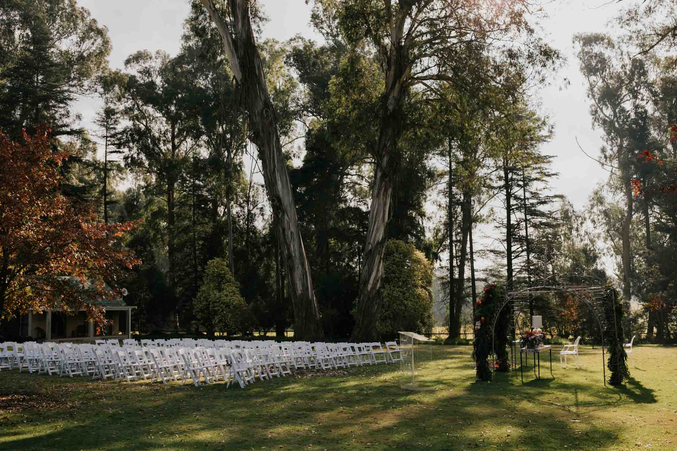 A wedding arch covered in orange purple and pink flowers like tulips and roses and lots of deep green leaves setup under the trees in the garden with white chairs