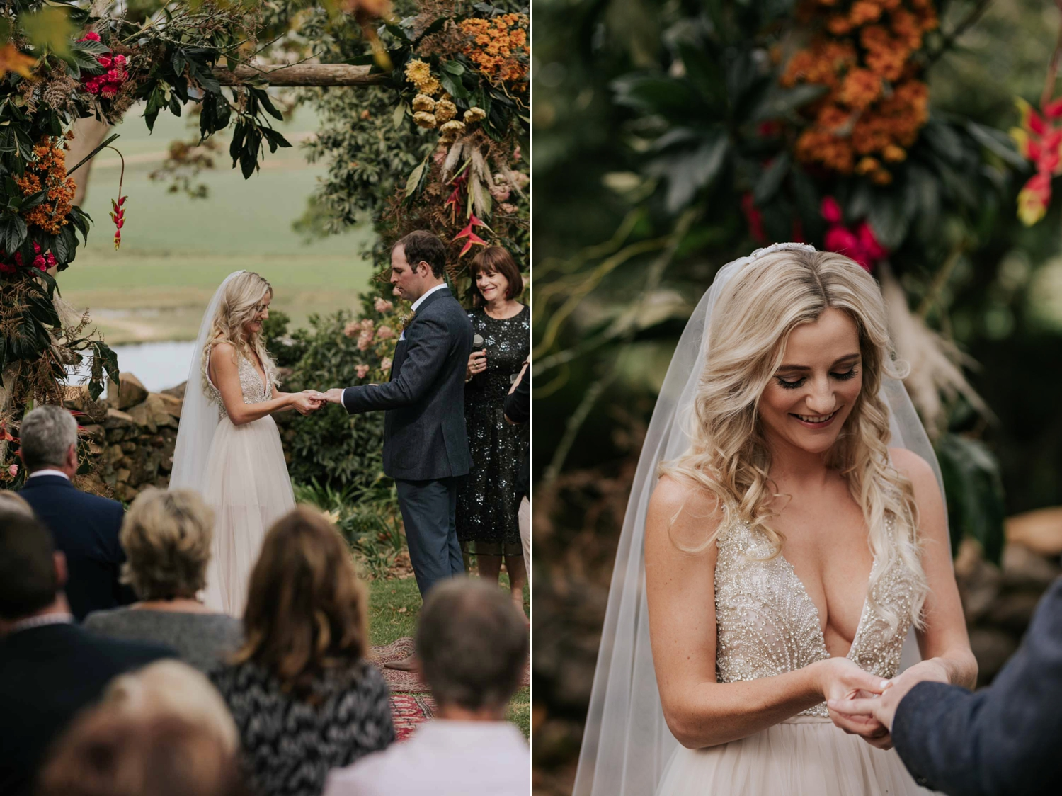 Bride putting a ring on groom's finger. Bride wearing a low cut dress with beautiful and detailed beadwork with a skirt that is see through and cute shorts underneath almost like a jump suit underneath a wedding dress. She is holding a wedding bouquet of burnt orange pink and red flowers and roses with dried ferns and grass in it.