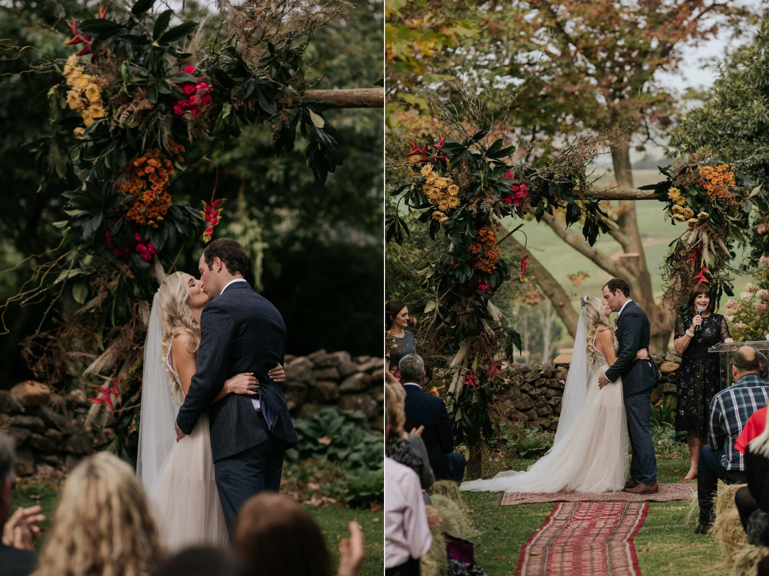 Bride and groom's first kiss under an arch of Autumn coloured flowers and roses on a farm with views in the background.
