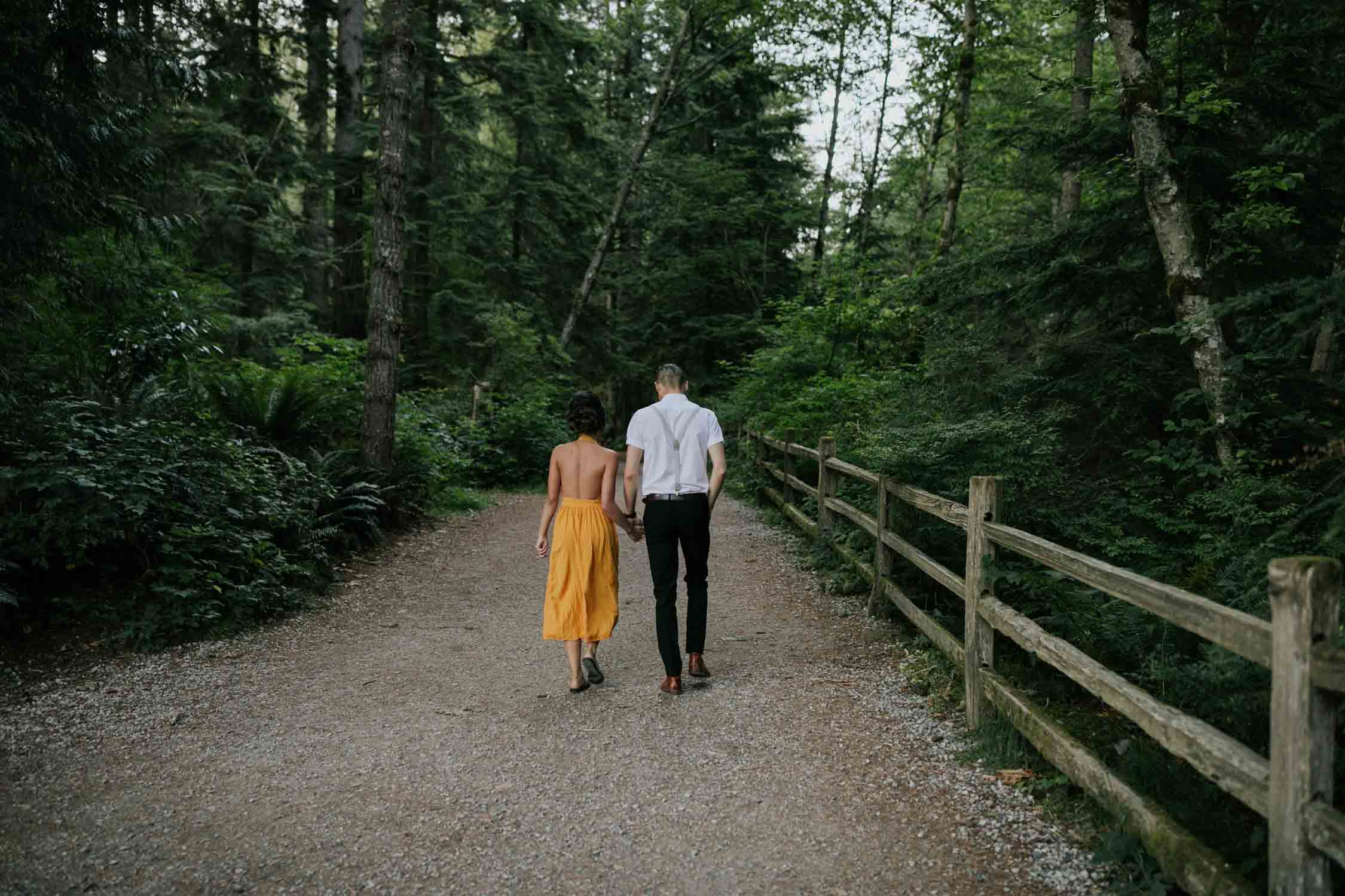 Engaged couple walk hand in hand down a path towards the forest at Rice Lake, Vancouver, BC.