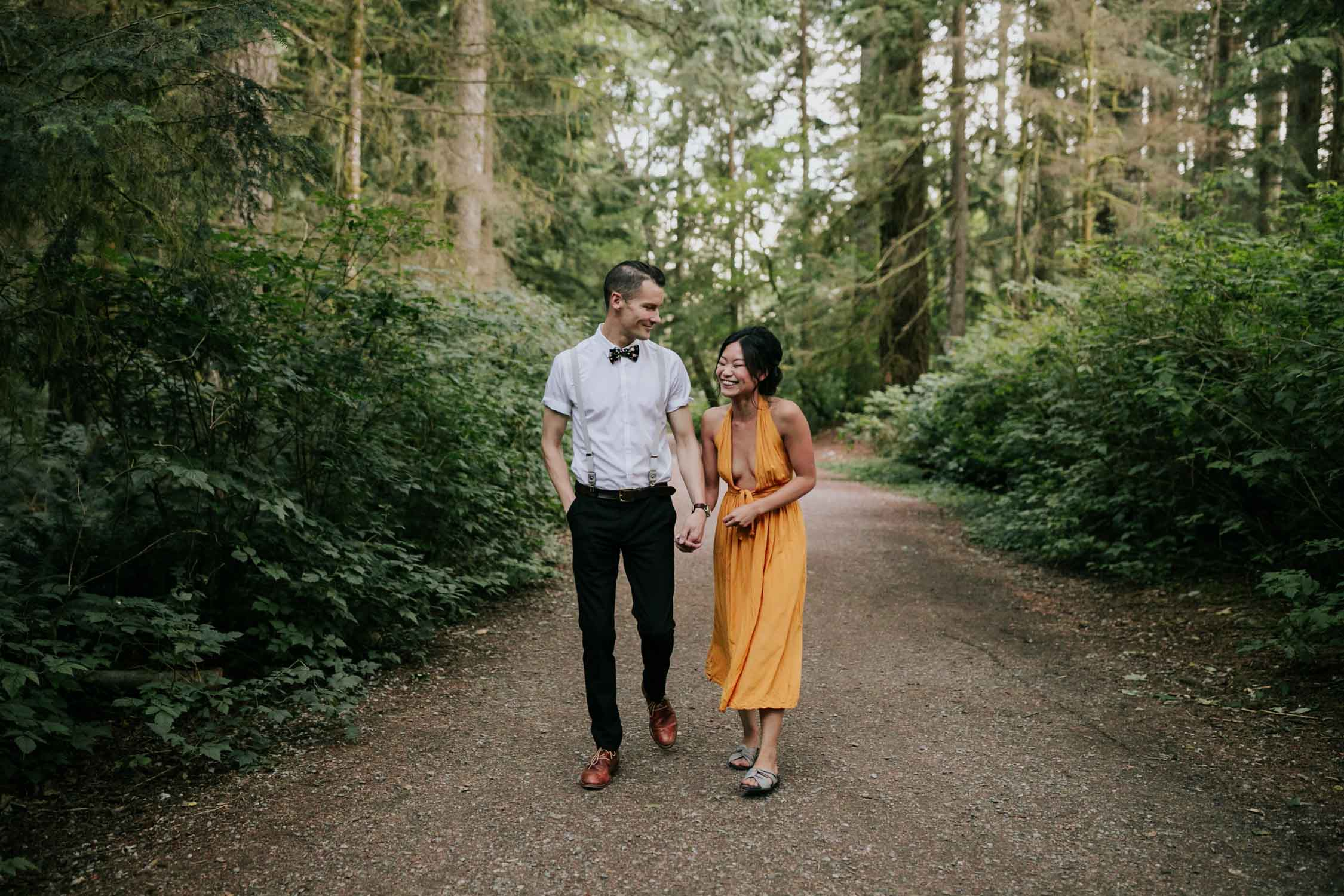 Engaged couple walk hand in hand down path in the forest near Rice Lake, Vancouver. She is wearing a yellow dress.