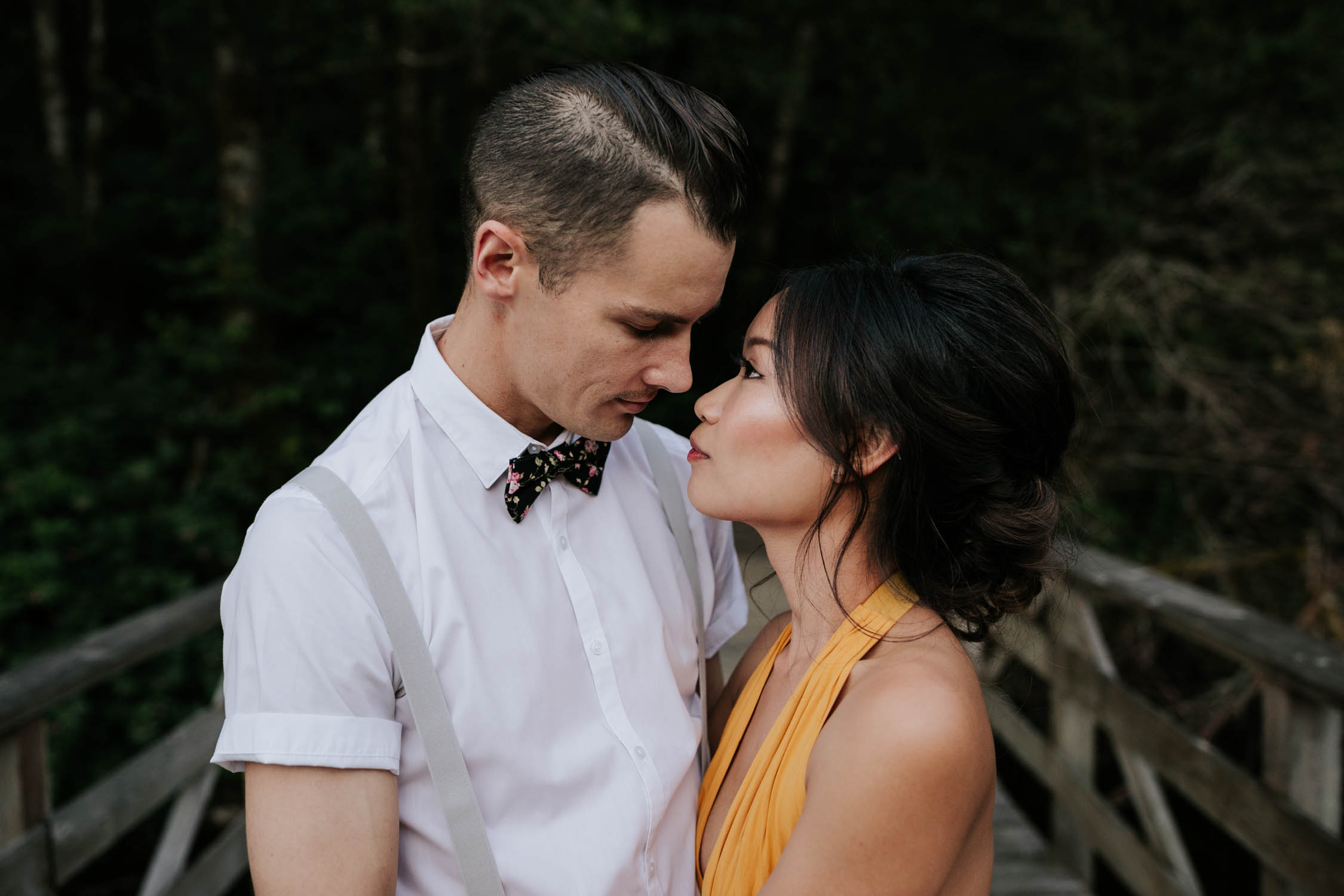 Engaged couple looking into each other's eyes. He is wearing a bowtie and she is wearing a yellow dress.
