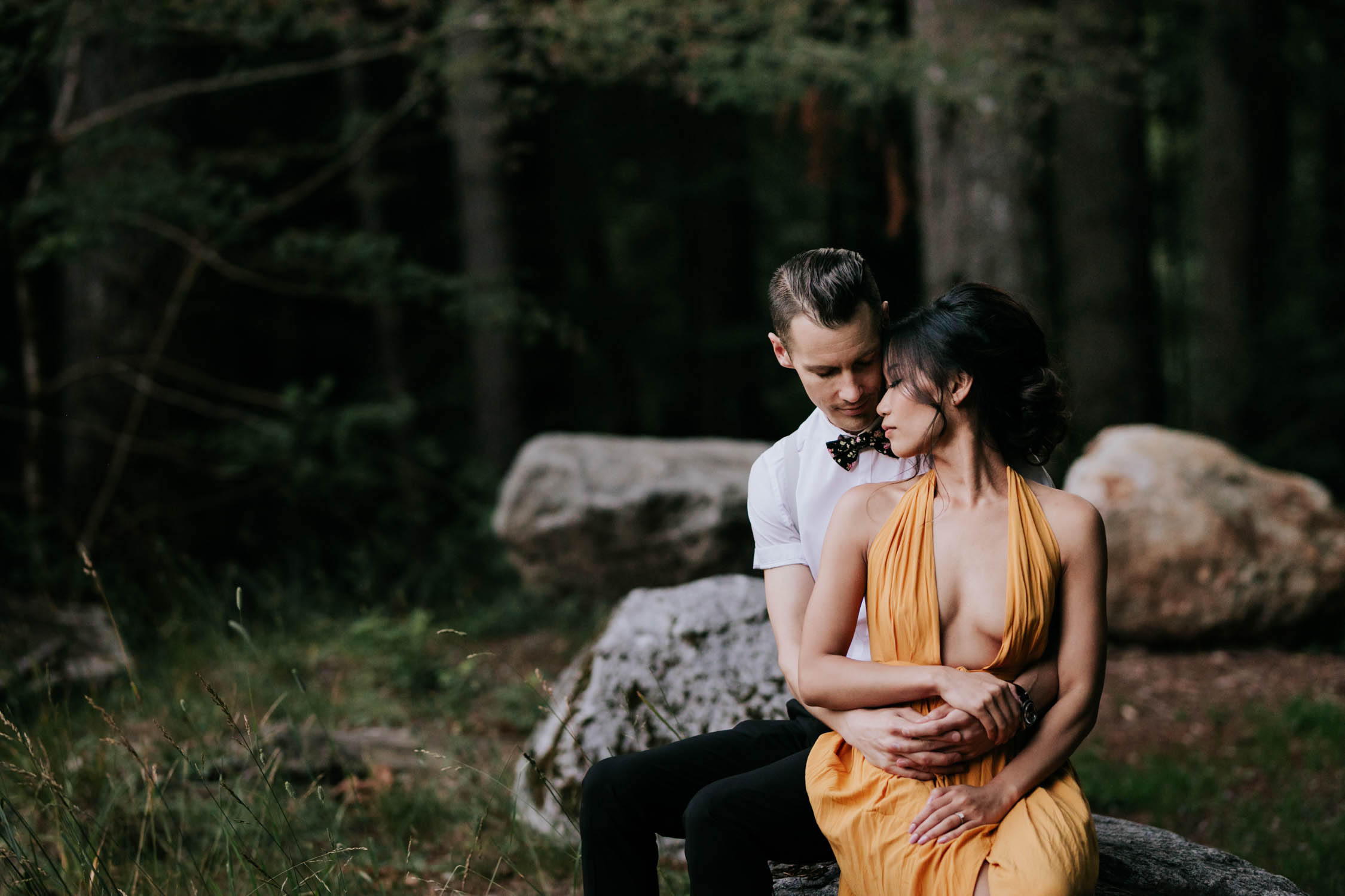 Couple sitting together on a rock in a forest. She is wearing a revealing yellow dress.