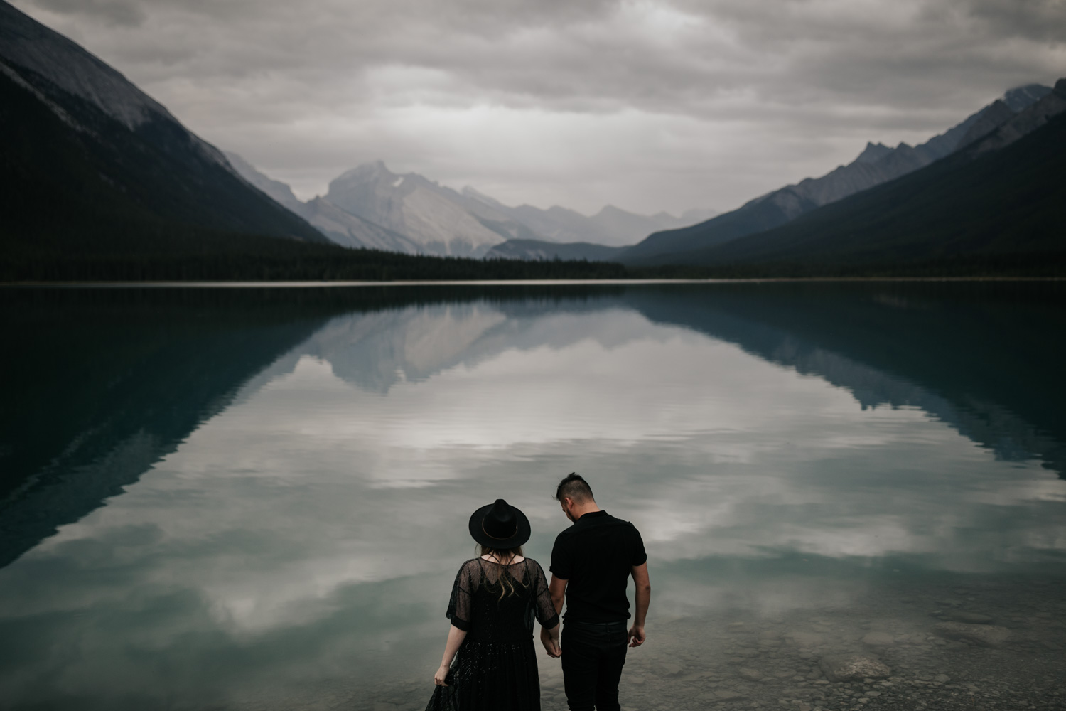 Boho Hipster Couple Stand In Front Of Turquoise Blue Lake Louise With Mountain Views