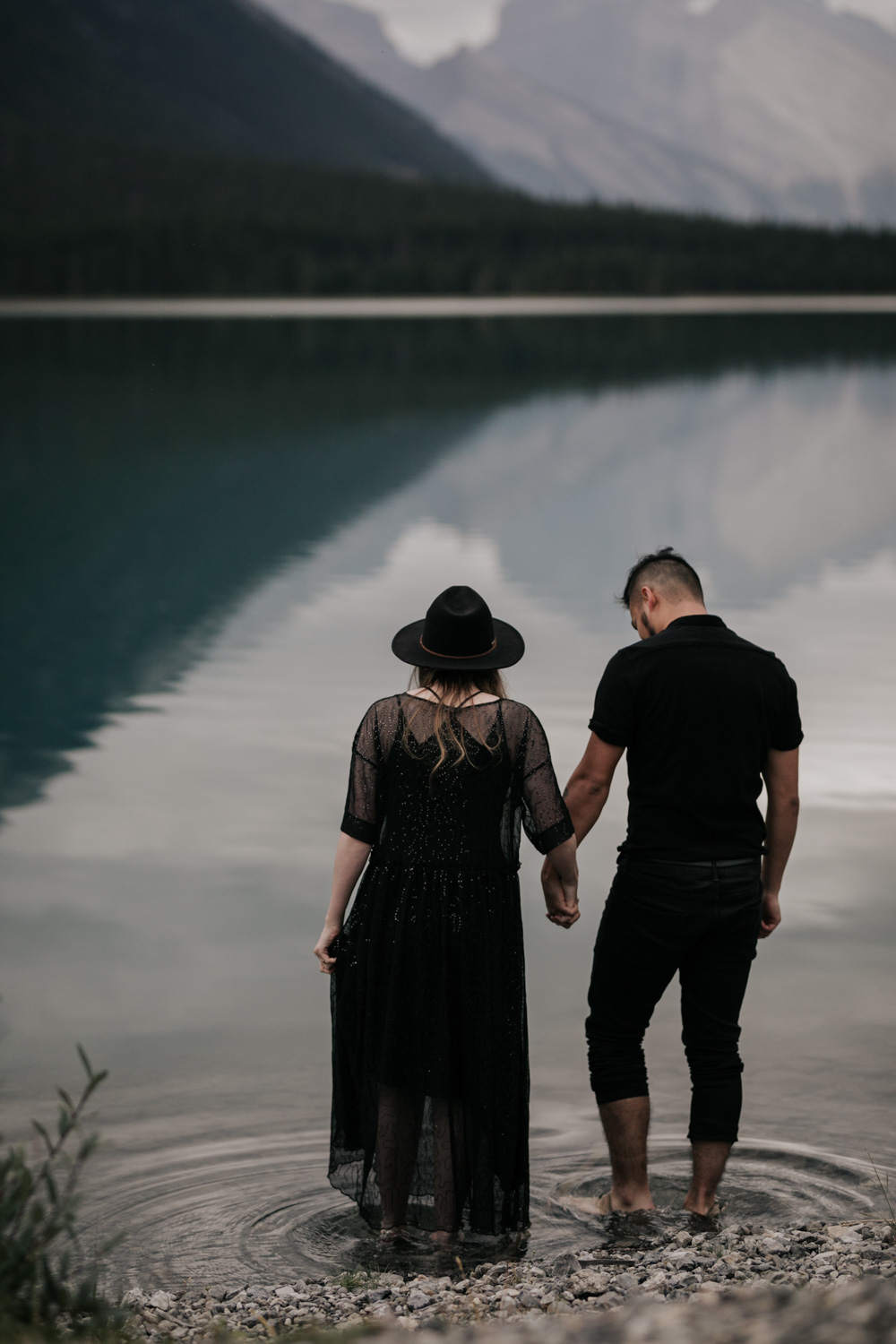 Boho Hipster Couple Stand In Turquoise Blue Lake Moraine With Mountain Views