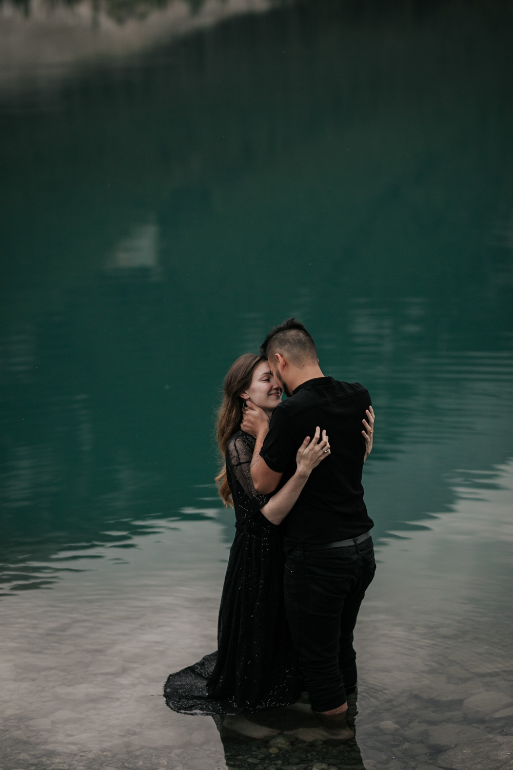 Engagement Photo Of Boho Couple Standing In Icy Cold Moraine Lake in Banff