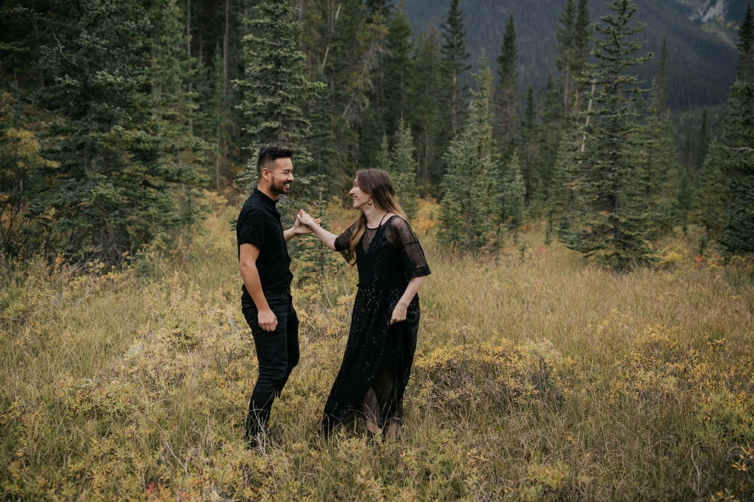 Engaged Hipster Alternative Couple Dancing In BC Forest And Yellow Field