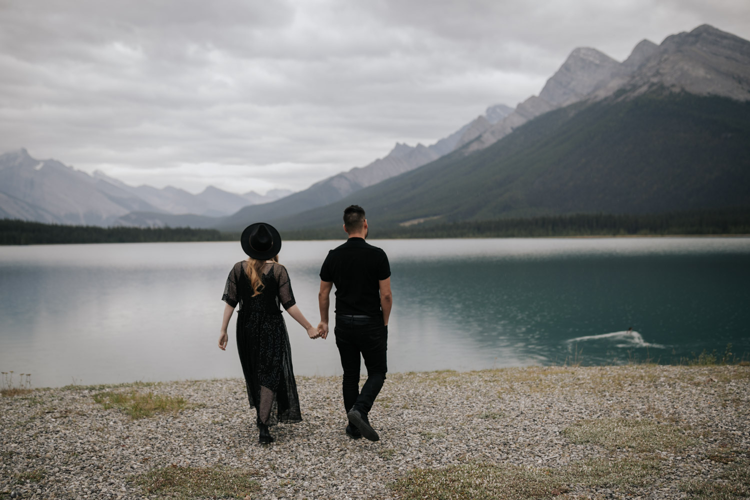Engaged Couple Walk Hand In Hand Towards Goat Lake In Canmore