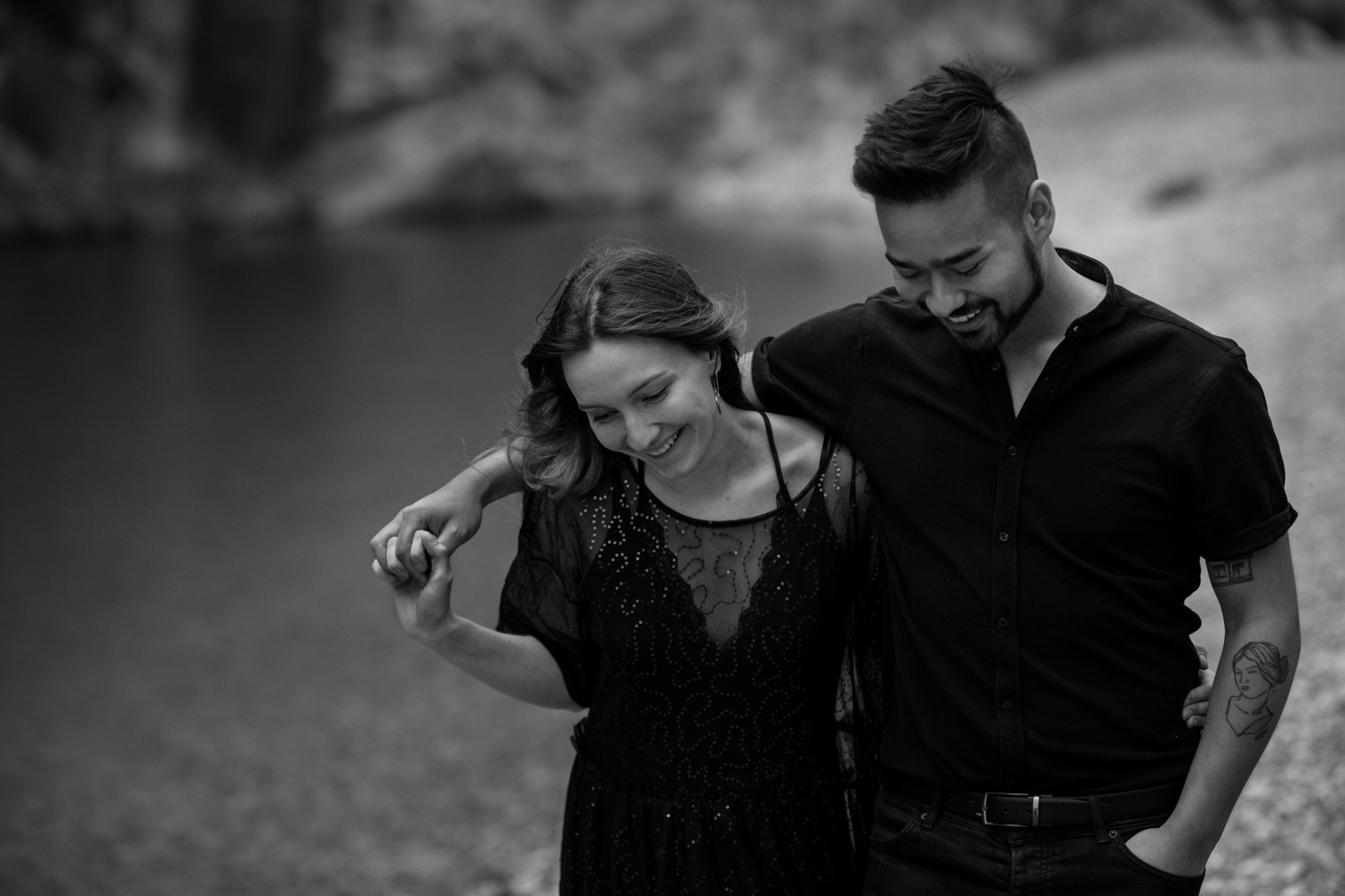 Couple Walks Along Turquoise Blue Banff Lake During Engagement Photo Shoot Session