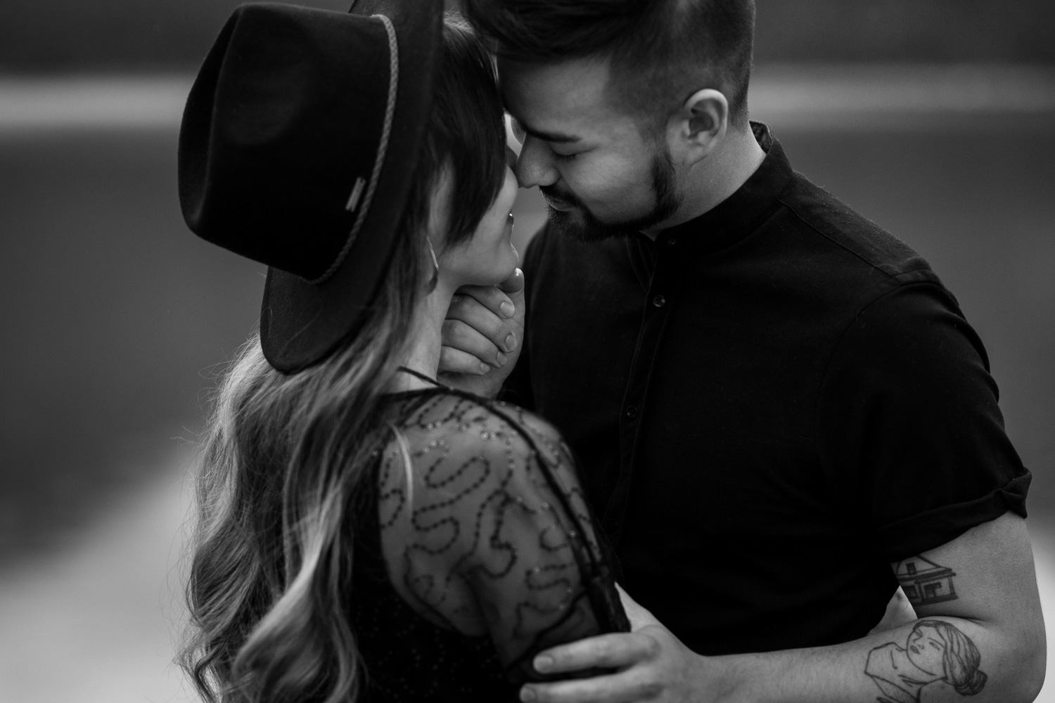 Boy Holds Girl Wearing Black Hipster Felt Hat Engagement Shoot