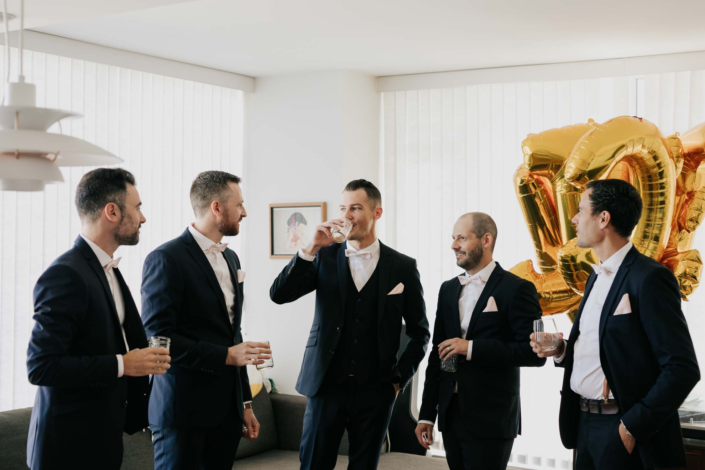Groom and groomsmen drinking whiskey and laughing together as they get ready in Vancouver loft apartment with epic mountain views