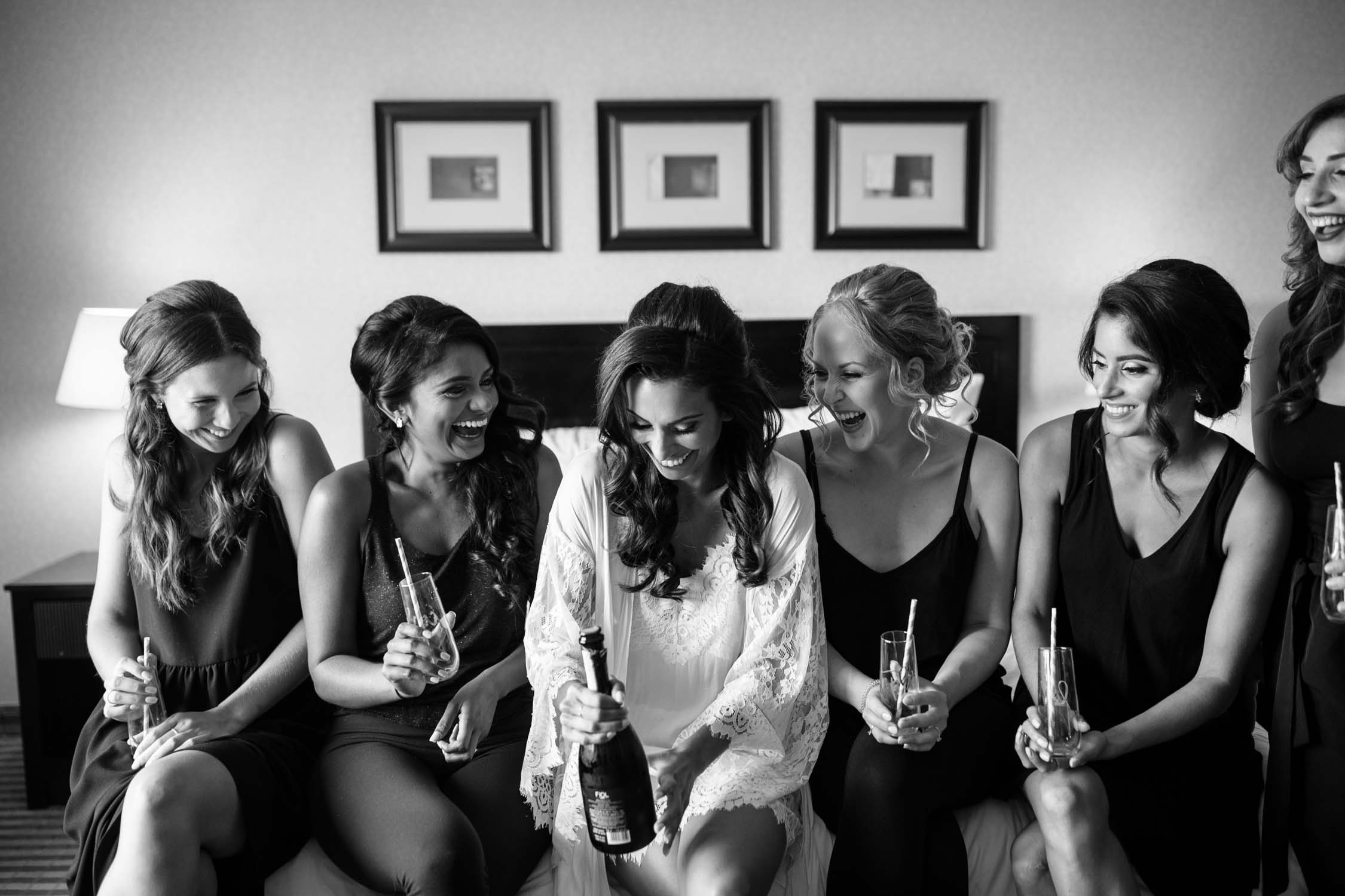 Bride and bridesmaids sitting on bed in their matching lace pjs drinking champagne before Newmarket Wedding at Madsen's Greenhouse.