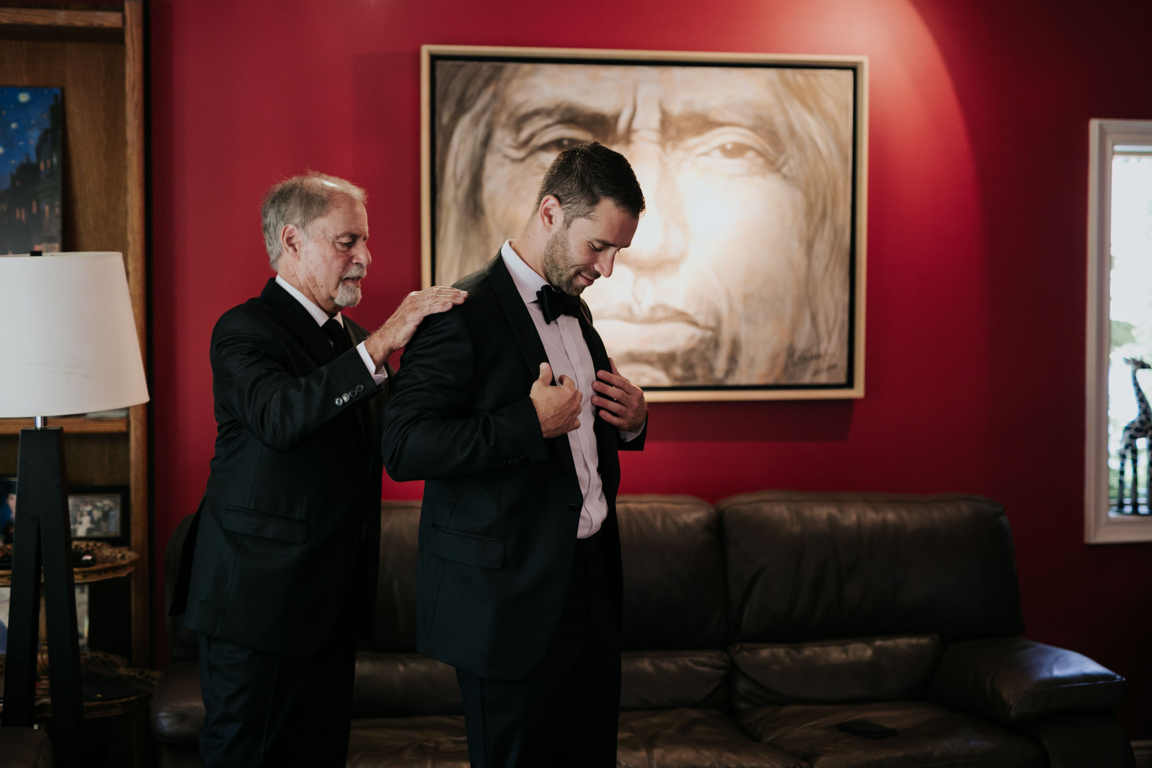 Documentary style getting ready scene of dad helping son put on his wedding jacket before Newmarket Wedding at Madsen's Greenhouse