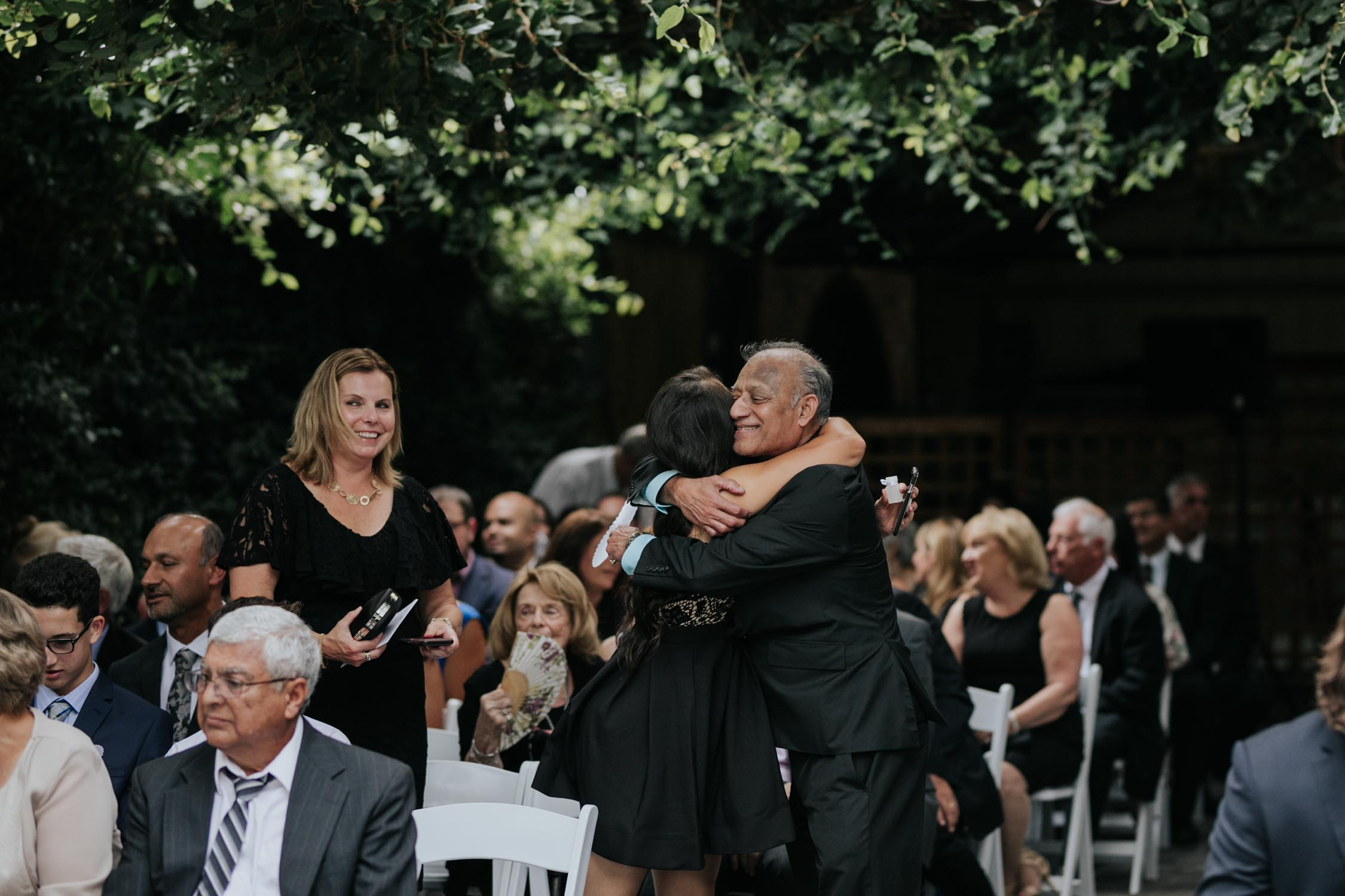 Happy candid photo of father of the bride greeting guests in Greenhouse chapel at Madsen's Greenhouse wedding venue in Newmarket close to Toronto