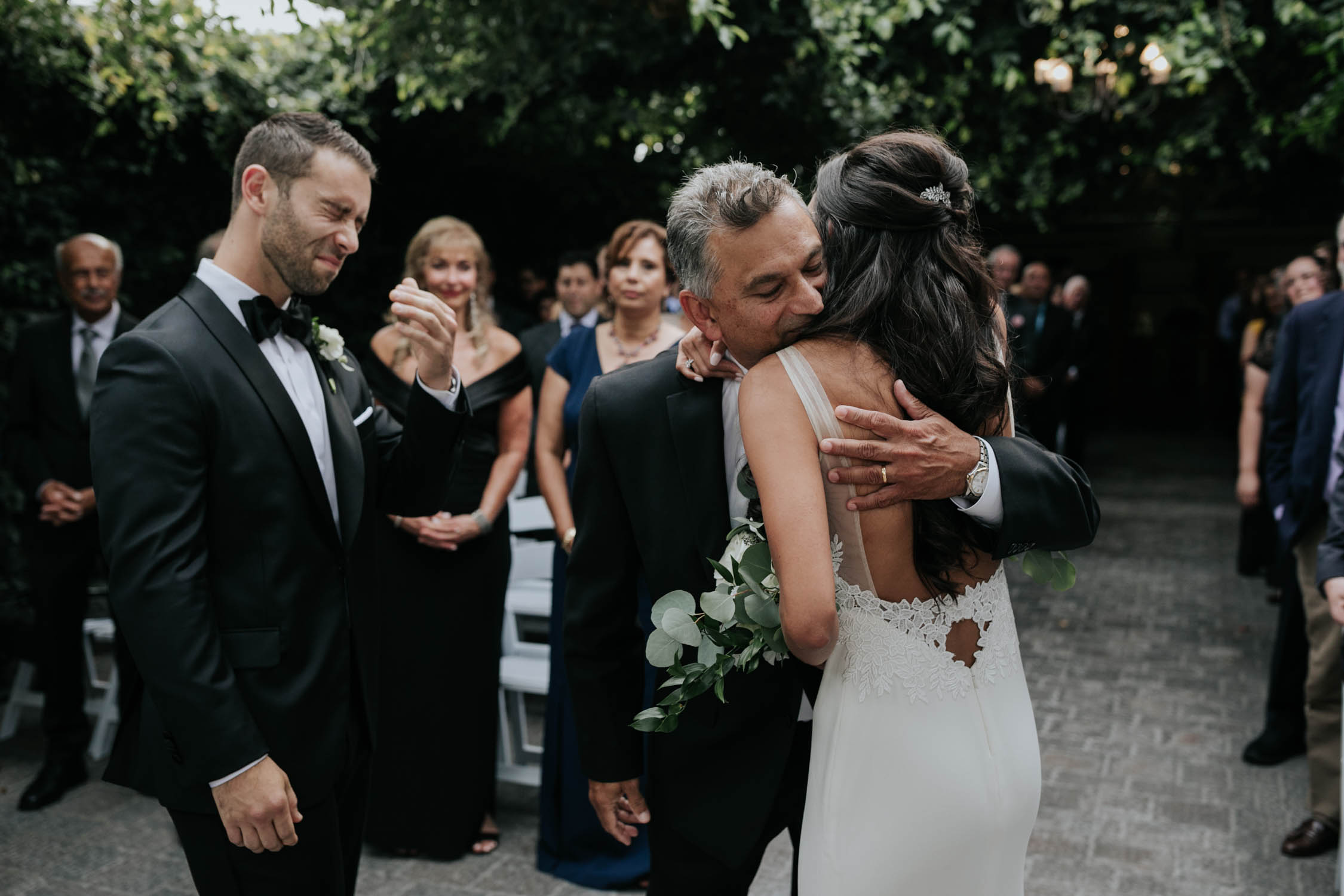 Emotional candid moment of groom crying as bride and father hug top of the aisle in Greenhouse chapel at Madsen's Greenhouse wedding venue in Newmarket close to Toronto