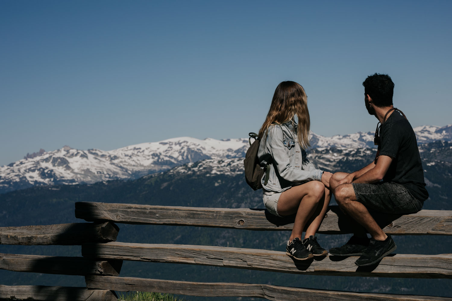 Couple sitting on a fence looking at the Whistler and Blackcomb mountain ranges after taking the Peak to Peak gondola up the mountain for their fun engagement session
