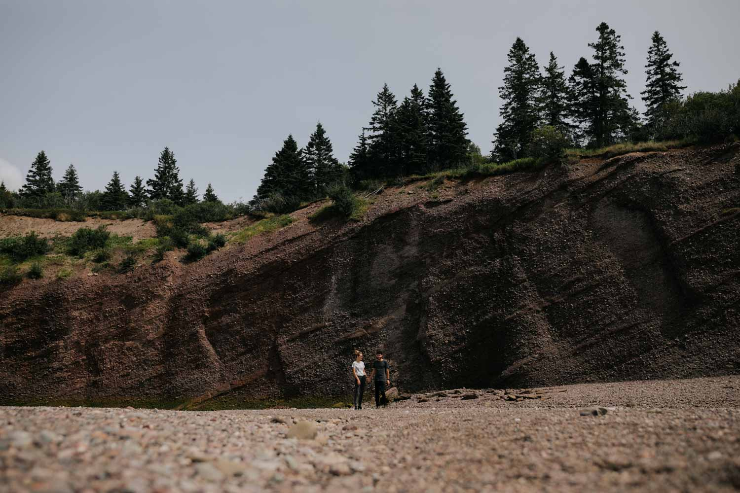 Couple stands in front of the breathtaking red sand cliffs at St. Martin's Sea Caves on the east coast of Canada during their engagement photo shoot