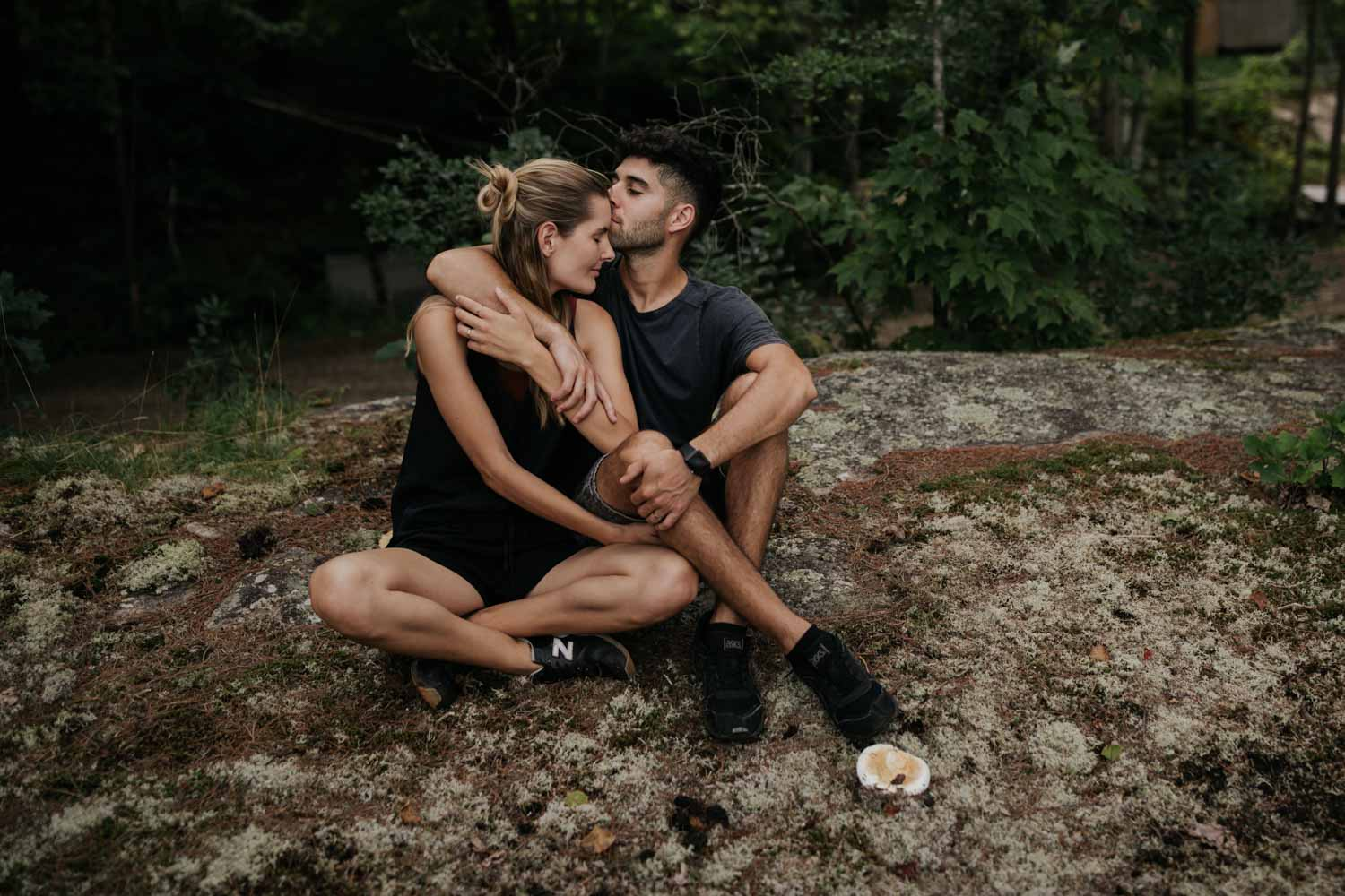 Intimate and candid photo of couple sitting together on a rock near a lake near a forest in North Vancouver
