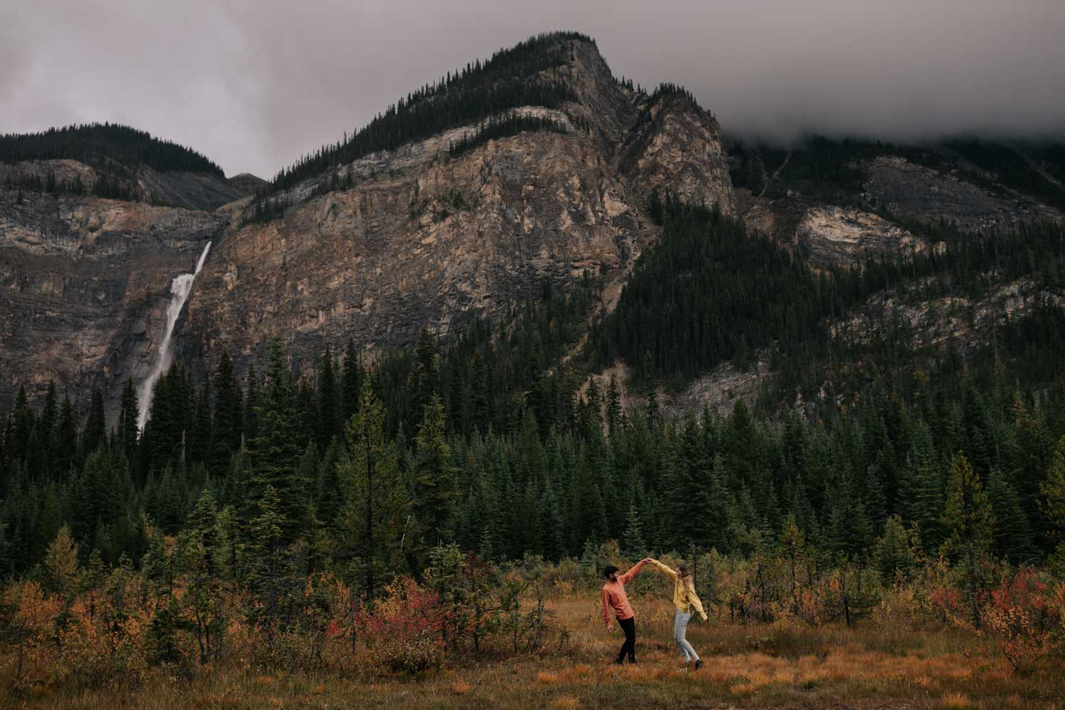 Couple dancing in the orange and yellow fields with the mountains and Takakkaw Falls is the background