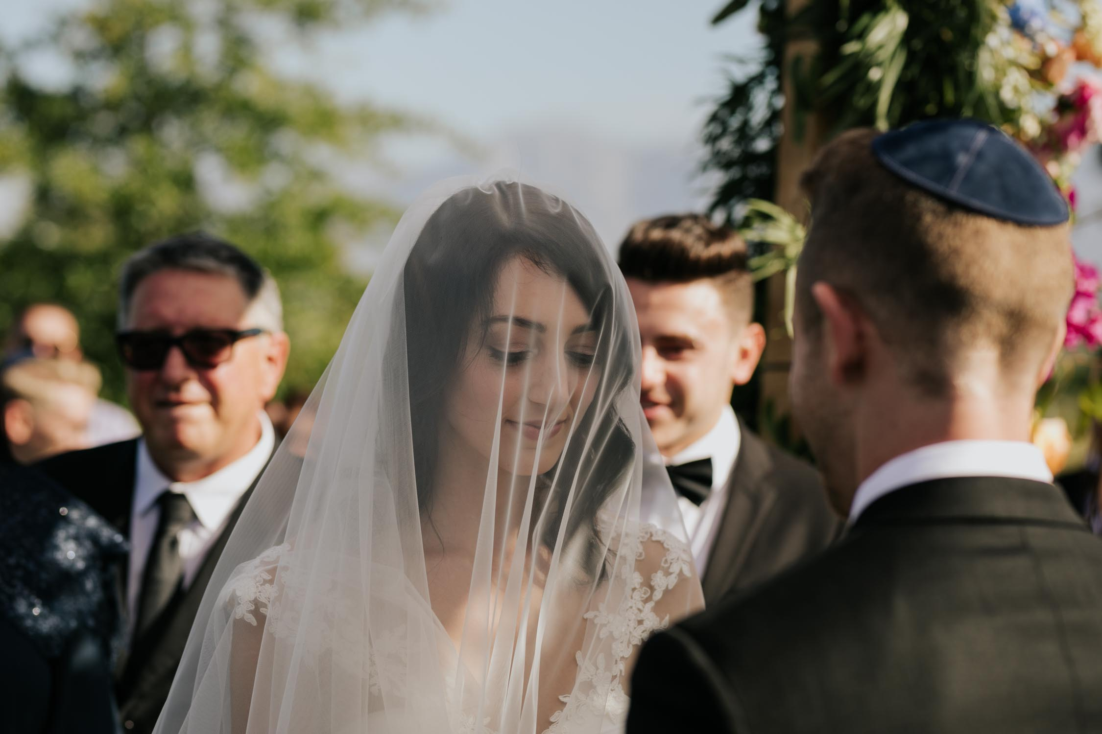 Bride and groom exchanges rings under the chuppah