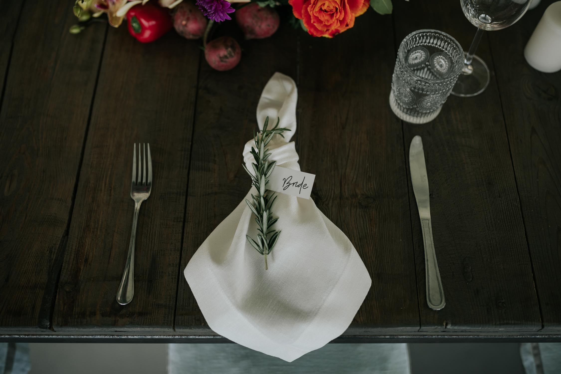 Wedding table setting knoted white linen napkin and rosemary sprig