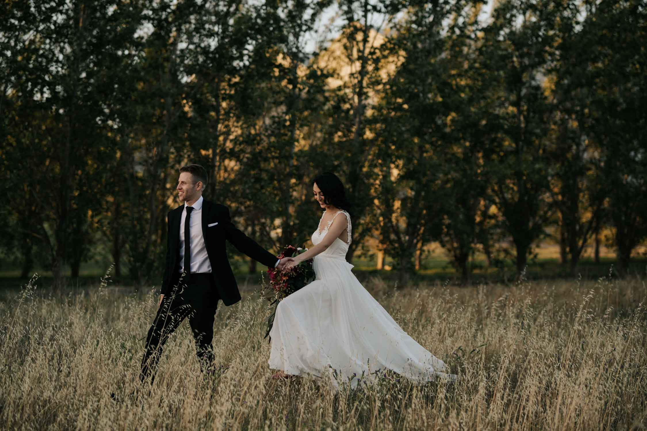 Bride and bridegroom walking in field at Belair Cape Town Wedding Venue