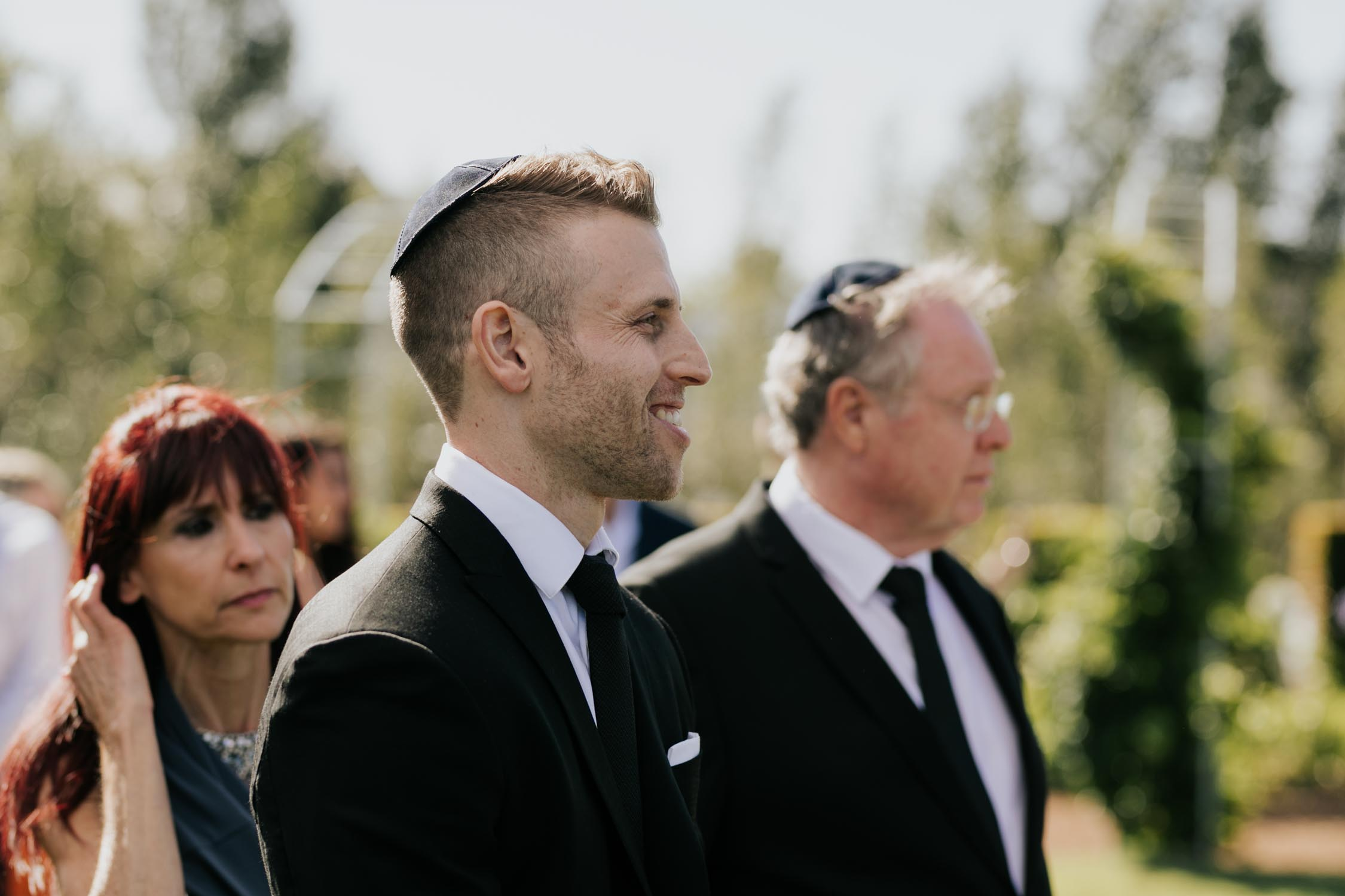 Jewish groom watches bride walk down the aisle