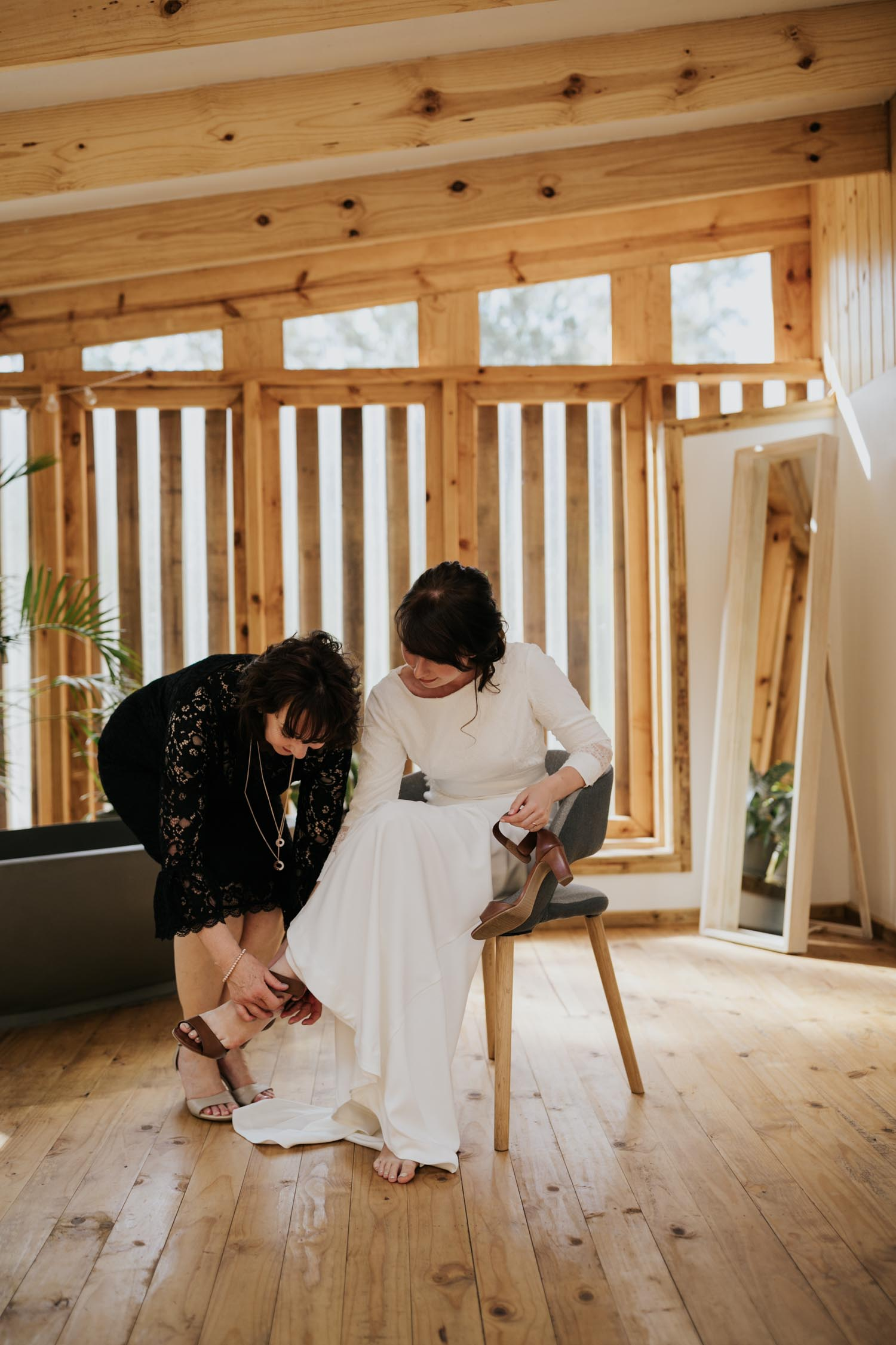 Bride's mom sits on Danish chair in Scandi loft apartment while the mother of the bride puts on her leather shoes