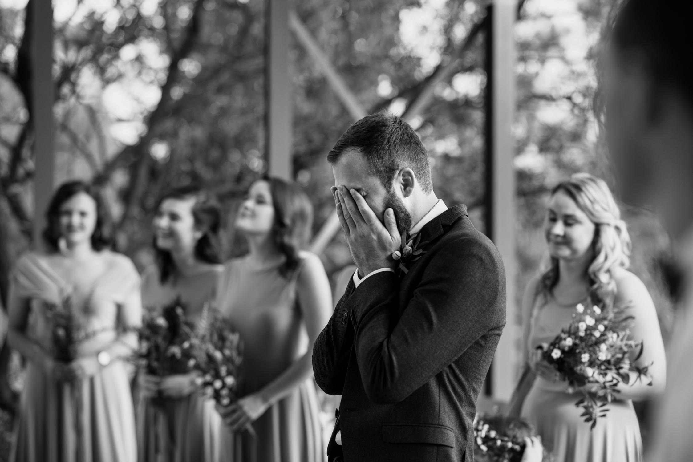 Photojournalistic photo of groom's emotional reaction as he watches his bride walk down the aisle