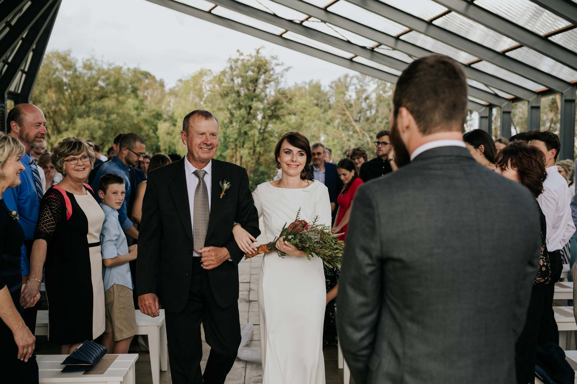 Emotional wedding moment when bride and father meet groom at the top of the aisle