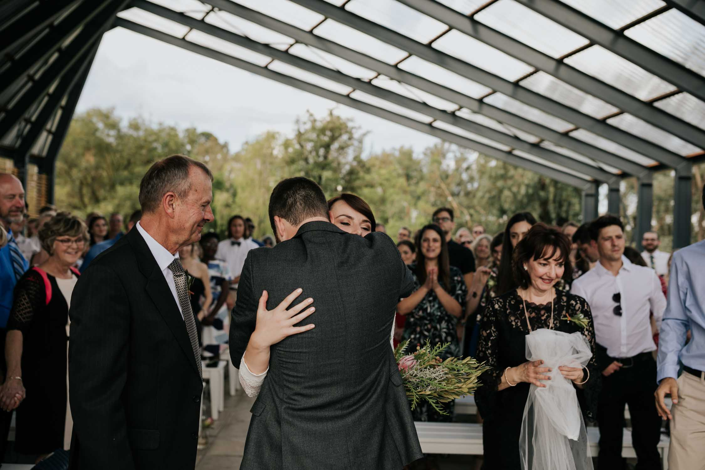 Emotional and raw wedding moment when groom hugs his bride at the top of the aisle