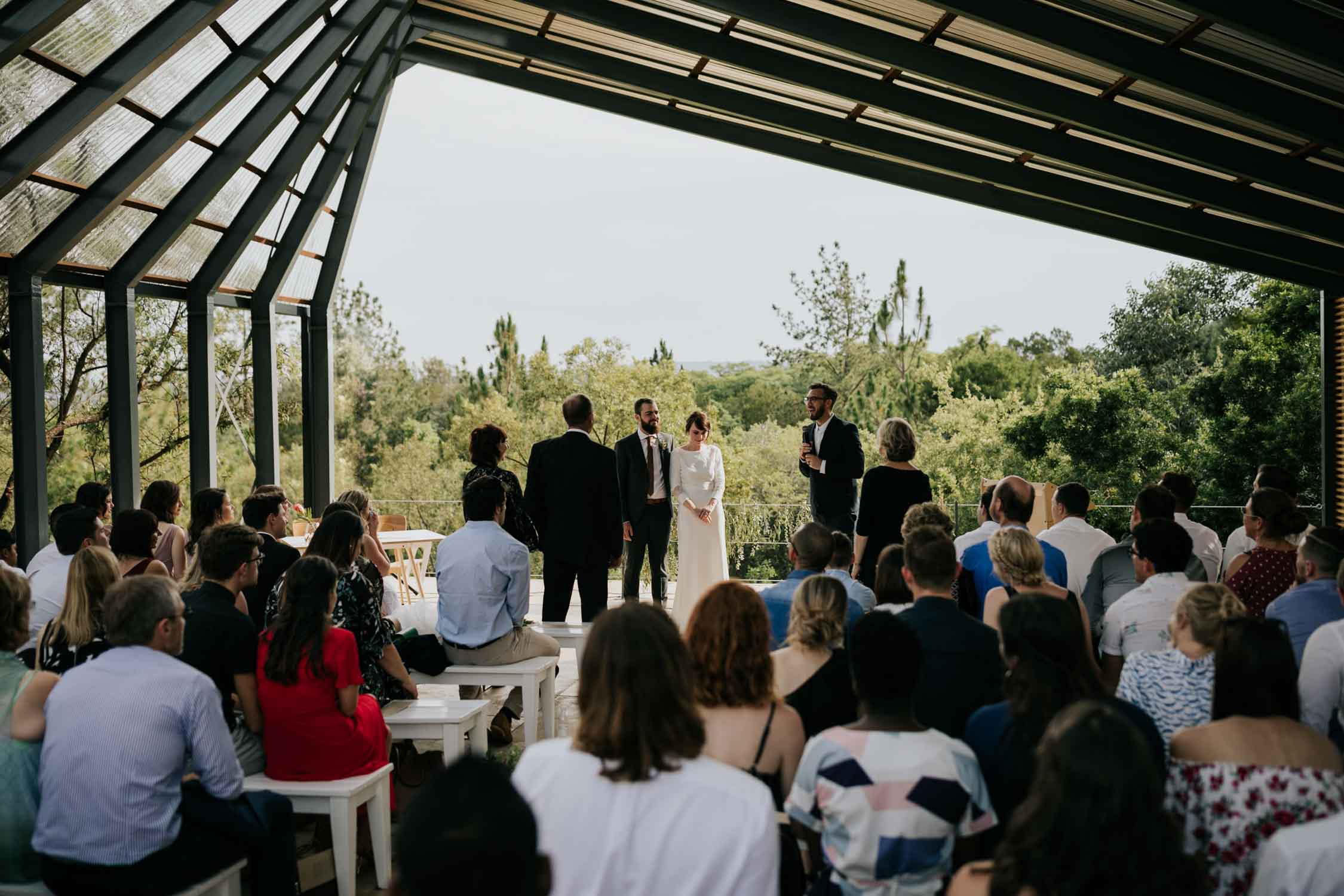 Parents of bride and groom stand to give them away during wedding ceremony in industrial modern geometric wedding venue