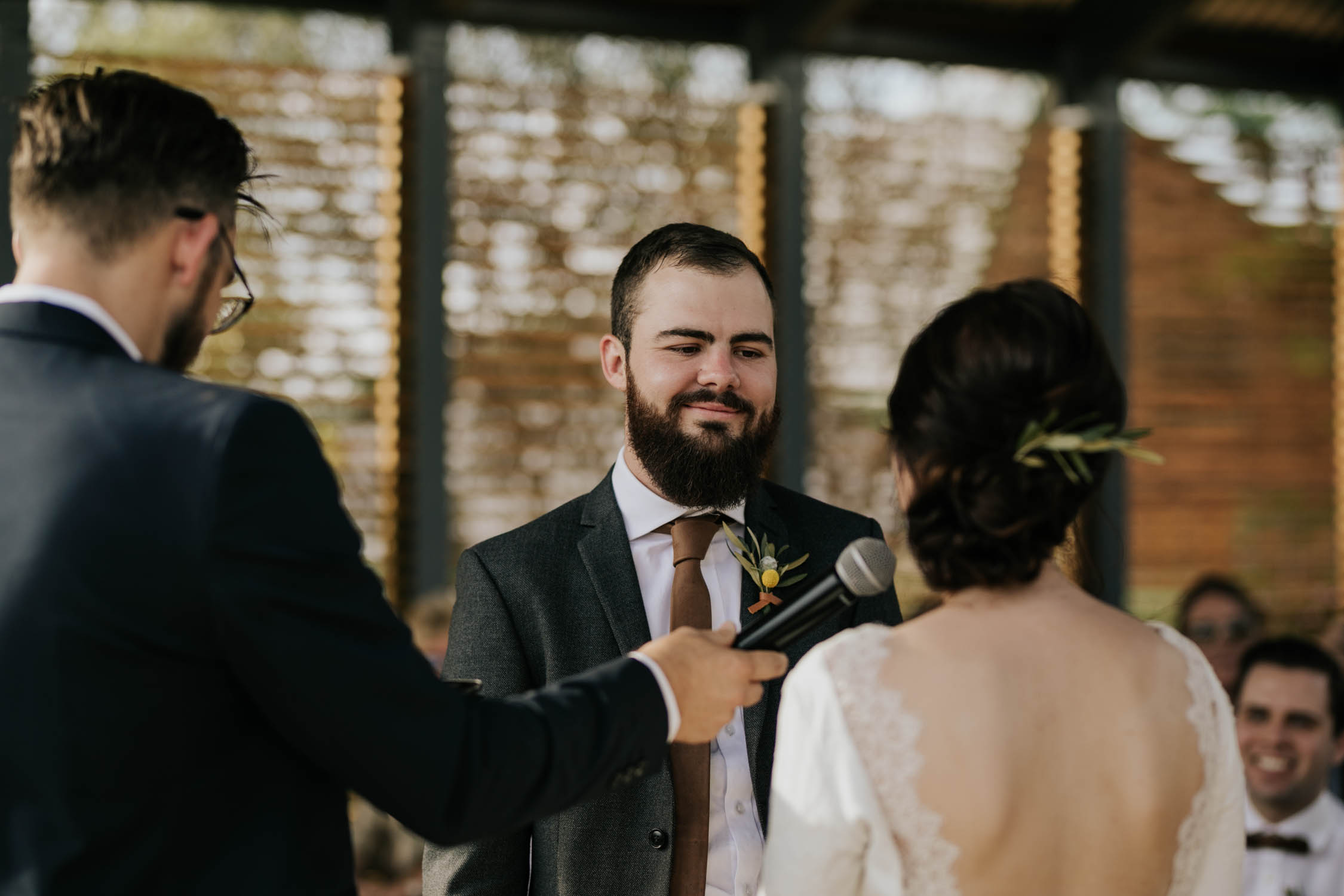 Hipster looking groom with beard wearing brown leather tie and modern boutineer listens to his wife saying her vows