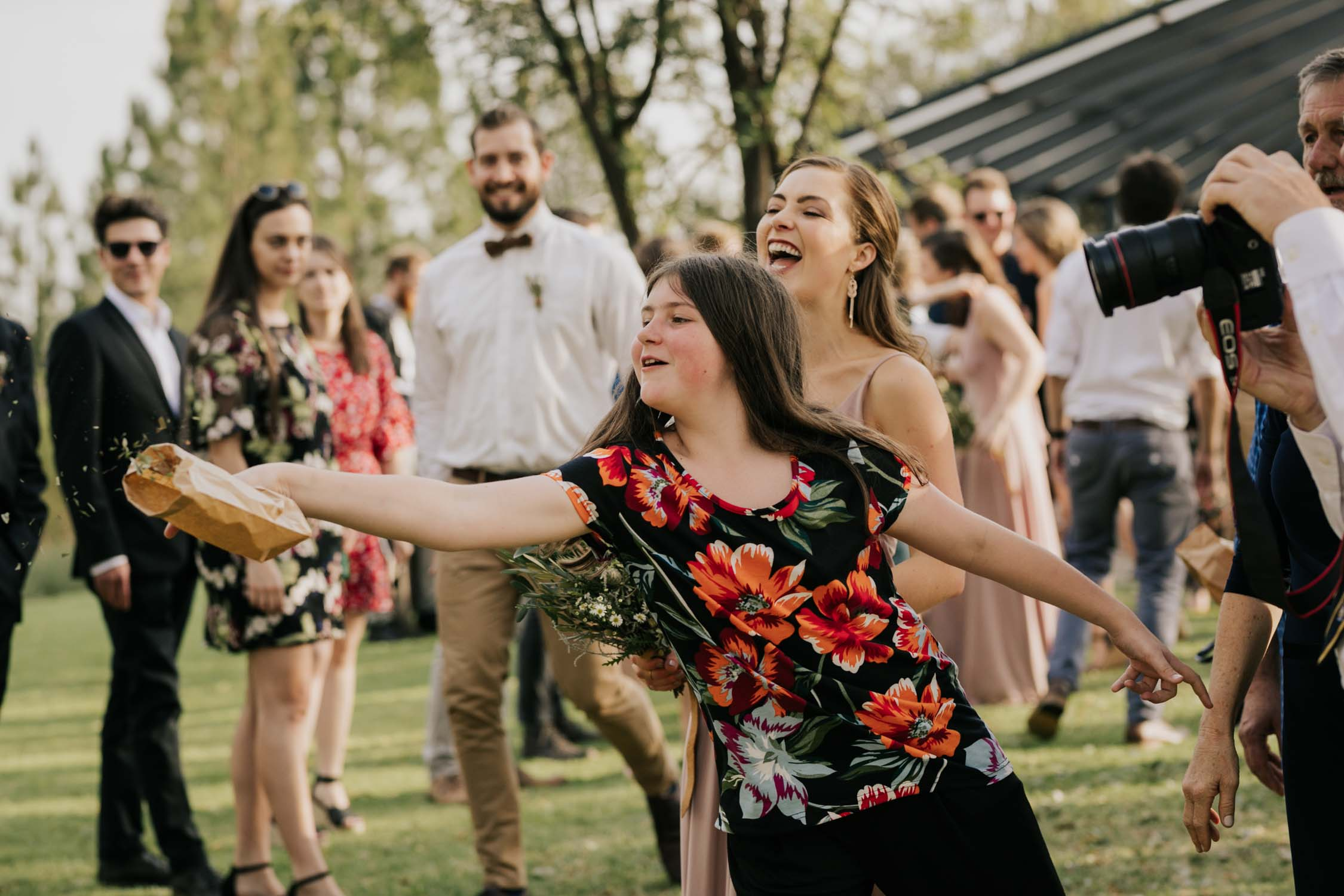 Cute photo of girl throwing confetti at newly married couple